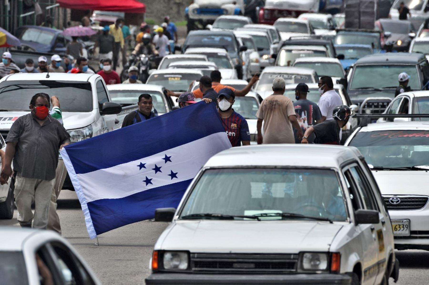 Los taxistas sostienen una bandera hondureña mientras bloquean un camino para protestar por la demanda de alimentos y ayuda económica en Tegucigalpa. Foto: AFP