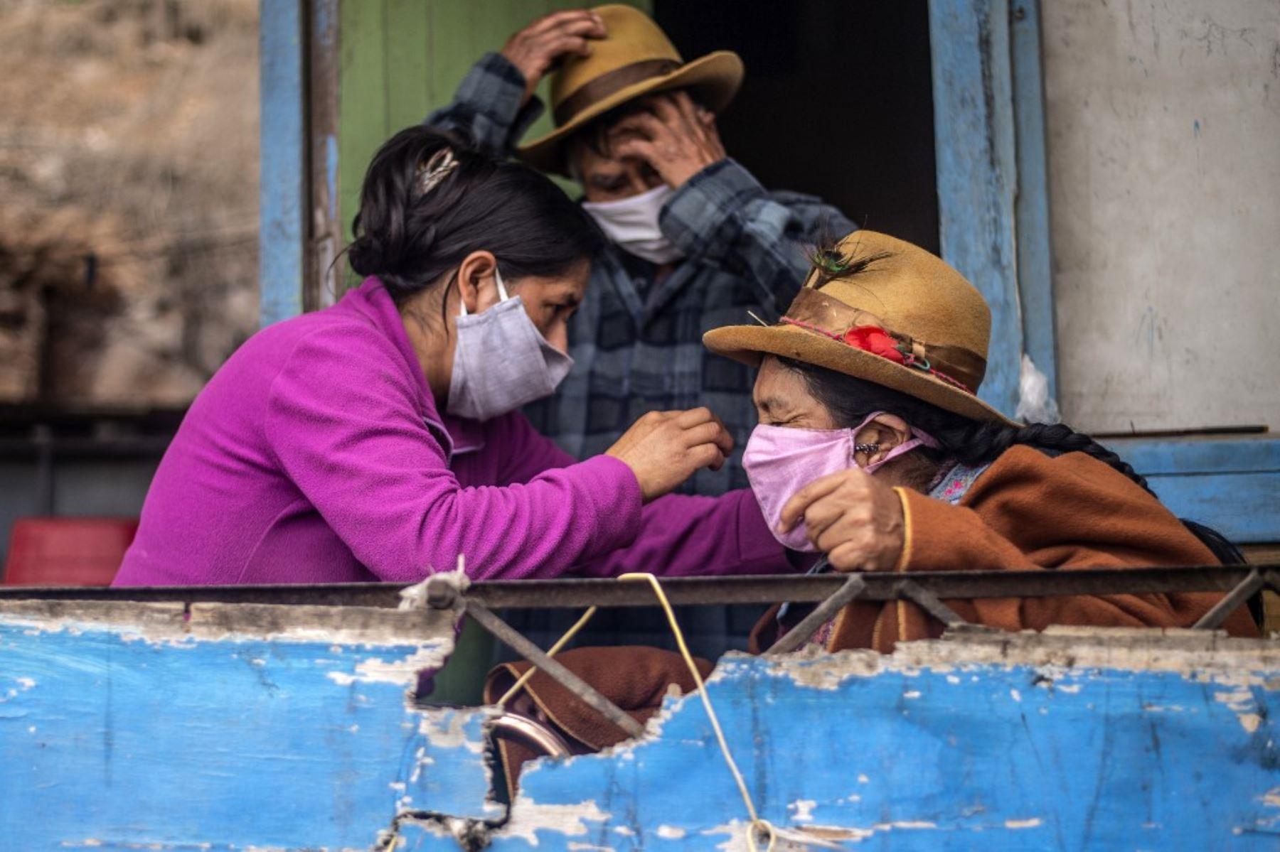Una mujer arregla la máscara facial de su madre en su casa de la sección de Pamplona Alta, Perú. Foto: AFP