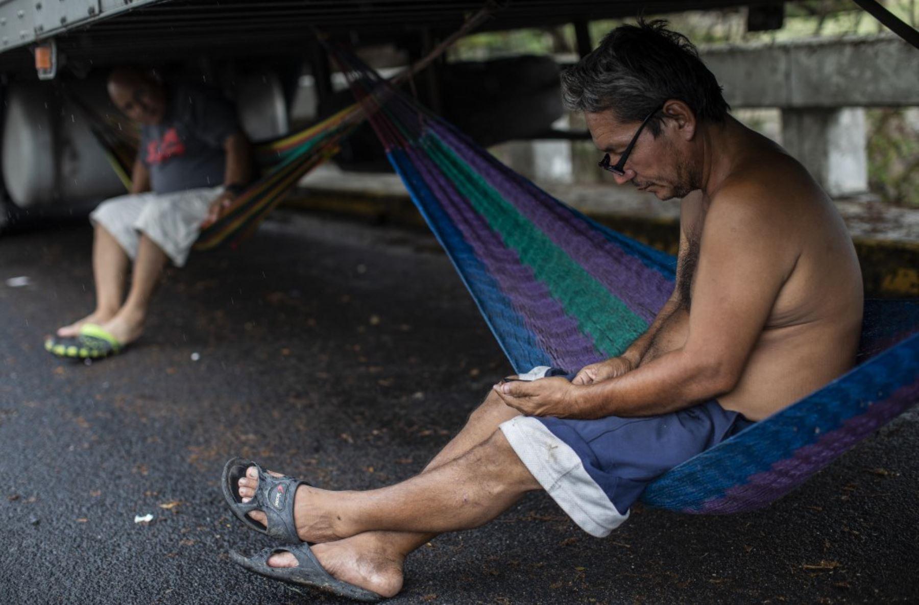 Un camionero revisa su teléfono sentado en una hamaca atada debajo de un camión durante un bloqueo en la frontera de Peñas Blancas entre Nicaragua y Costa Rica, en Rivas, Nicaragua. Foto: AFP