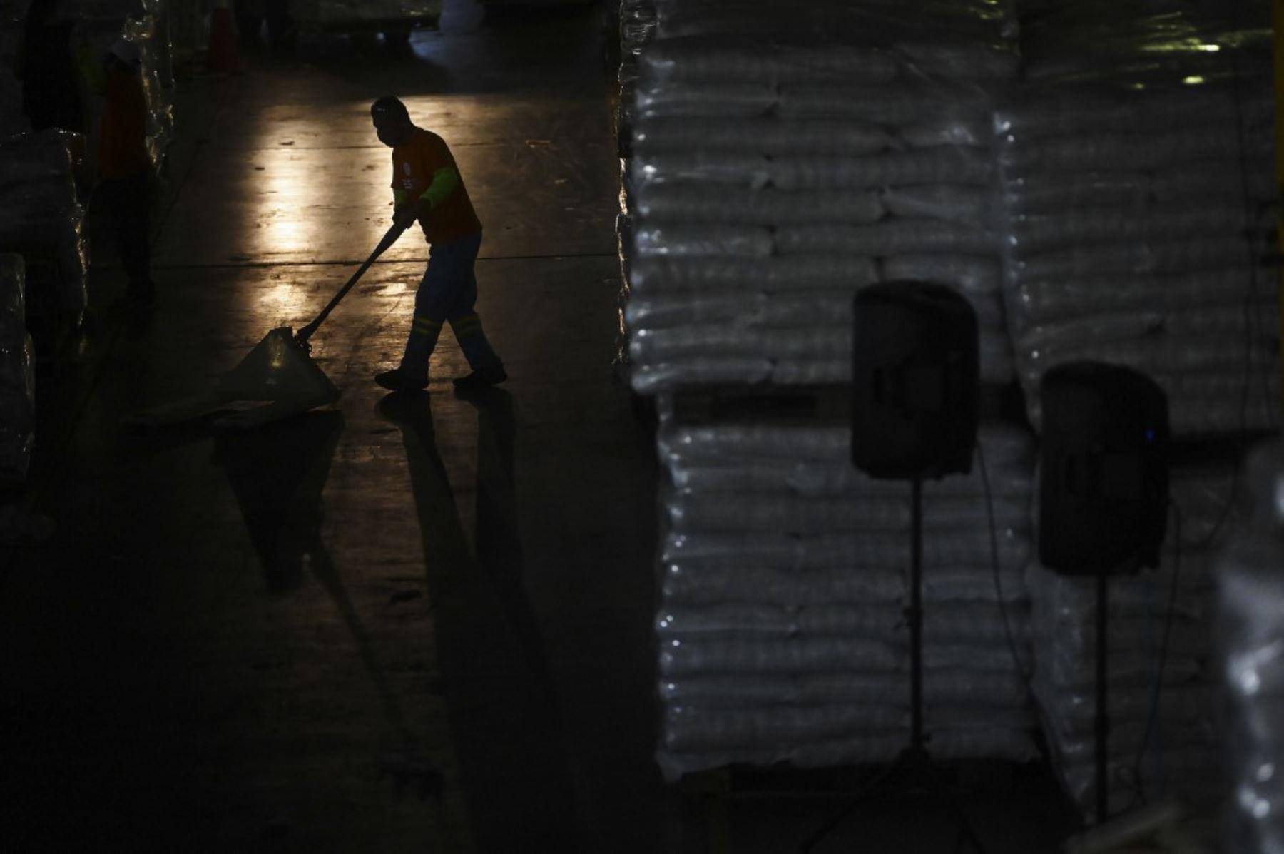 Los trabajadores y voluntarios del gobierno almacenan y distribuyen paquetes con alimentos que serán entregados a las familias económicamente afectadas durante la cuarentena especial decretada por el gobierno debido a la pandemia de coronavirus COVID-19, en Ilopango, El Salvador. Foto: AFP