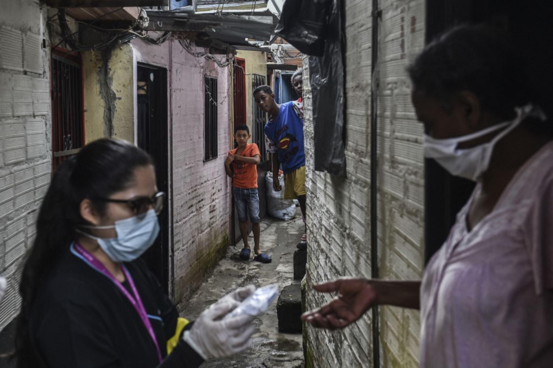 Un trabajador de la salud distribuye máscaras faciales a los locales como medida preventiva contra la propagación del nuevo coronavirus COVID-19, en el barrio de Santa Cruz en Medellín. Foto: AFP