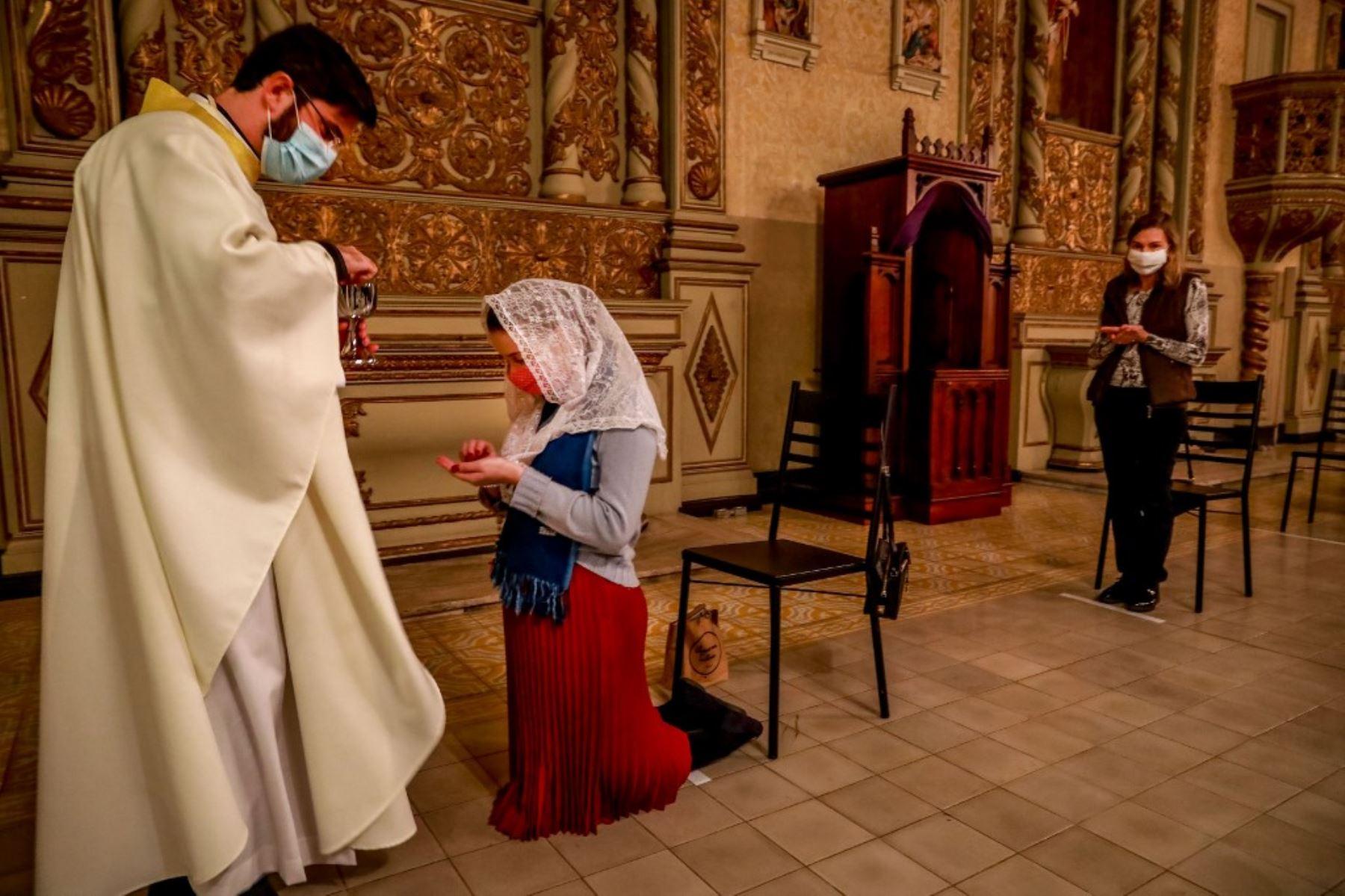El sacerdote Lucas Mendes, con una máscara protectora, da la comunión a una  mujer durante la misa en la iglesia Nossa Senhora das Dores en Porto Alegre, en el sur de Brasil. Foto: AFP