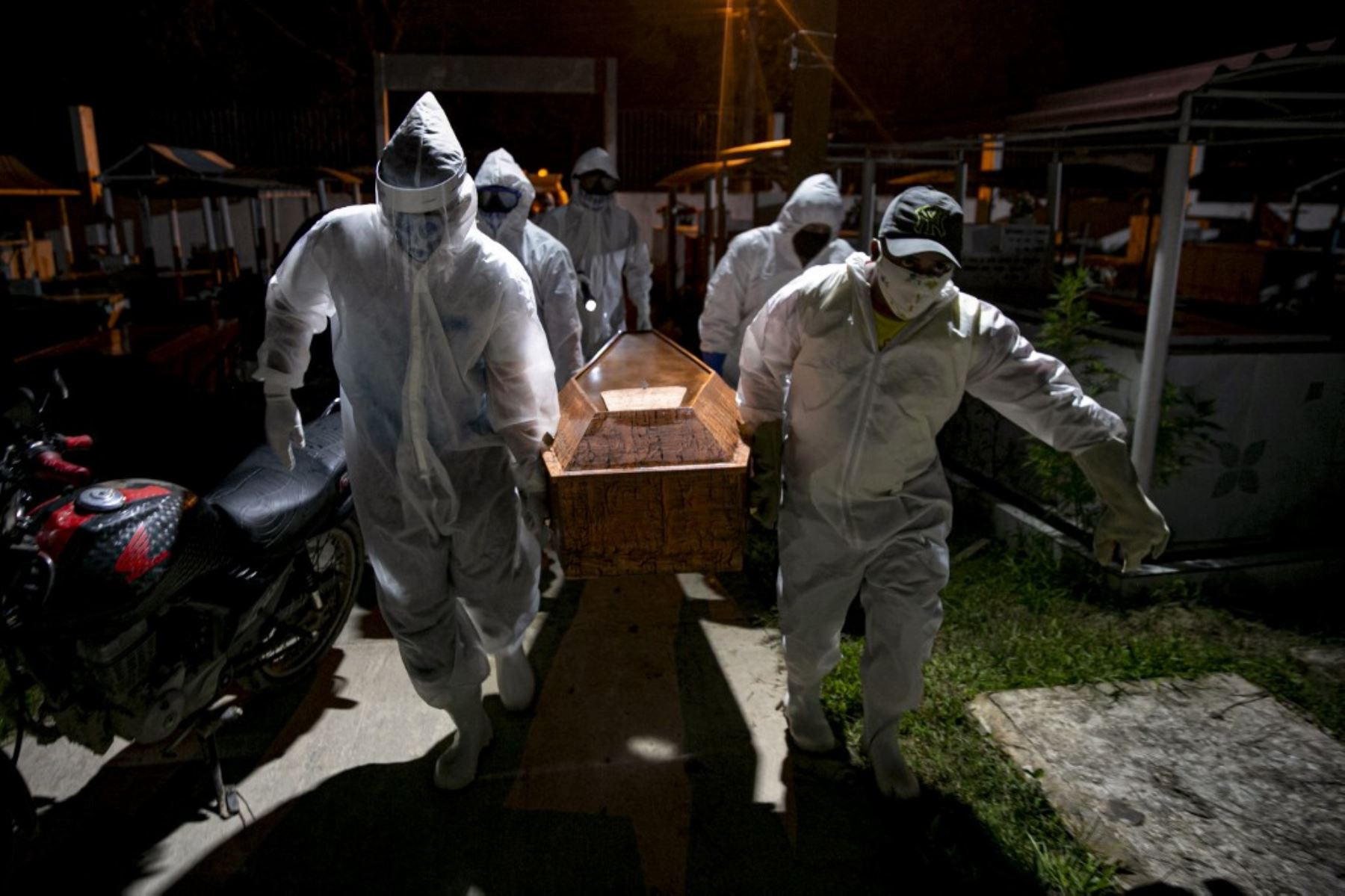 Los sepultureros con ropa protectora llevan el ataúd de una víctima del nuevo coronavirus COVID-19 para su entierro en el Cementerio Municipal de Recanto da Paz en la ciudad de Breves, Brasil. Foto: AFP