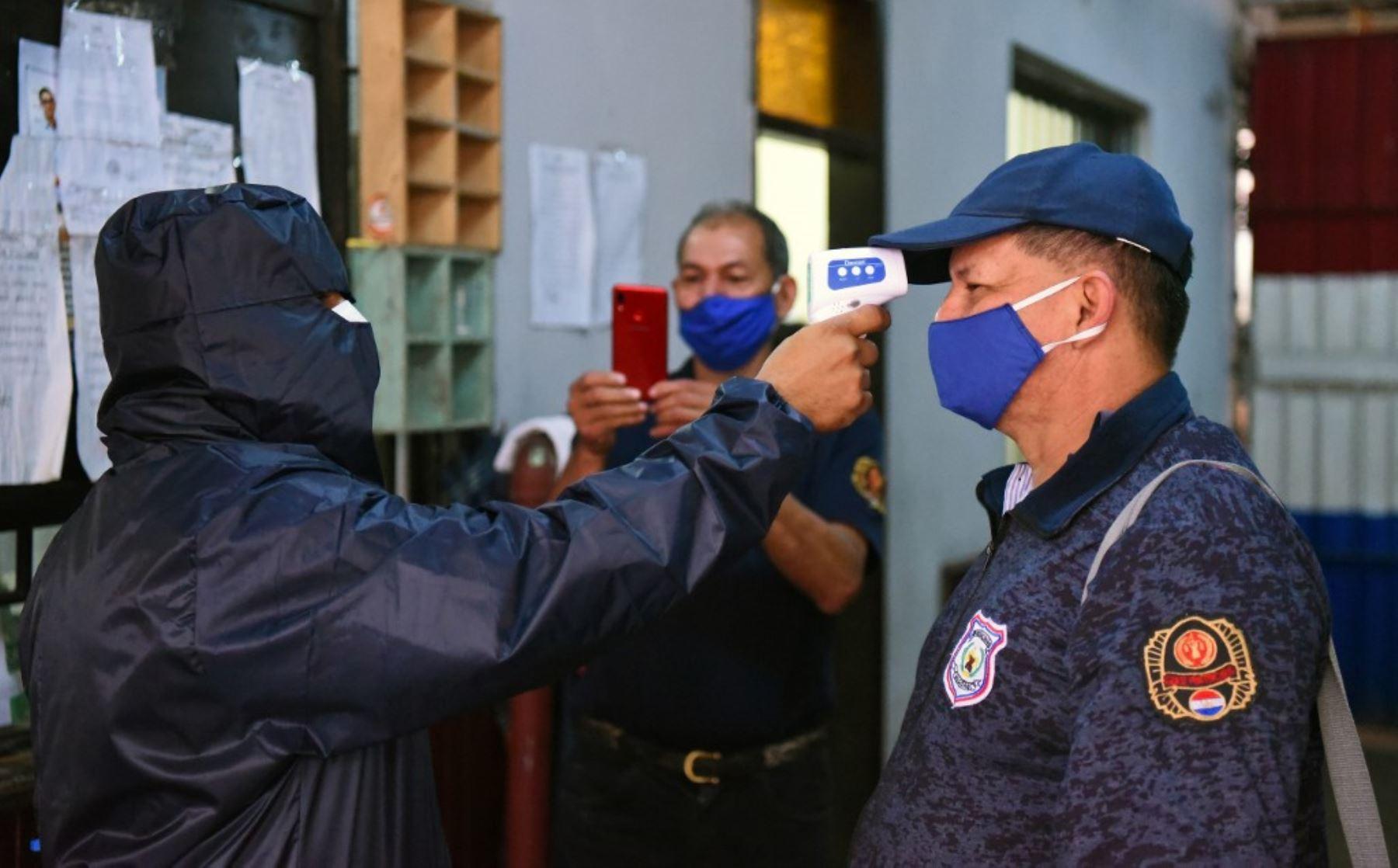 Un trabajador de salud toma la temperatura del personal en la prisión de Tacumbu en Asunción. Foto: AFP