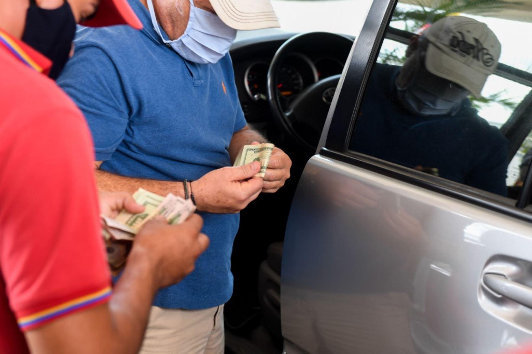 Un hombre con una máscara facial paga en una estación de servicio en Caracas en medio de la pandemia de coronavirus Covid-19. Foto: AFP