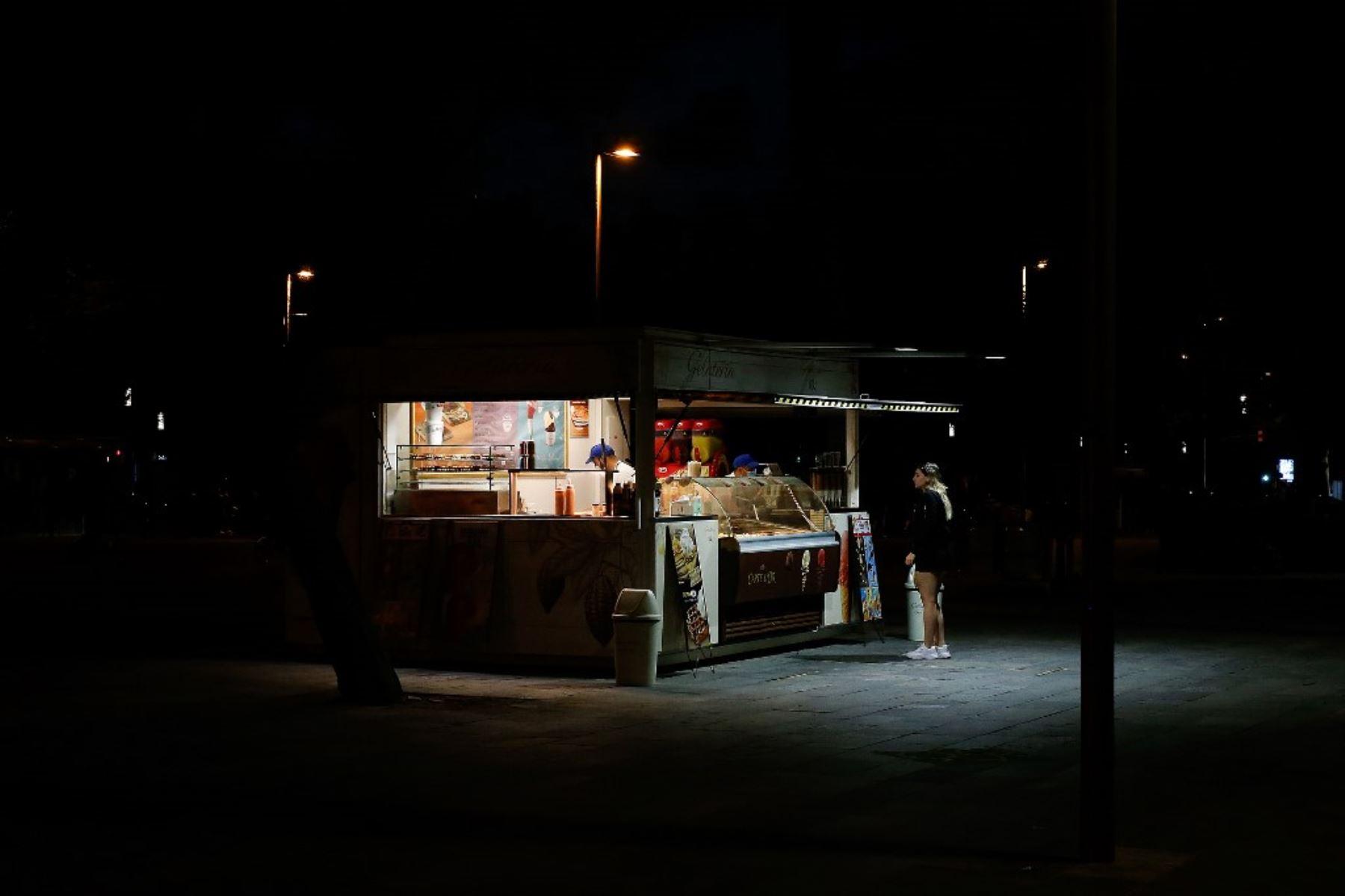 Una mujer compra helado en un puesto en la playa de la Barceloneta en Barcelona. Foto: AFP
