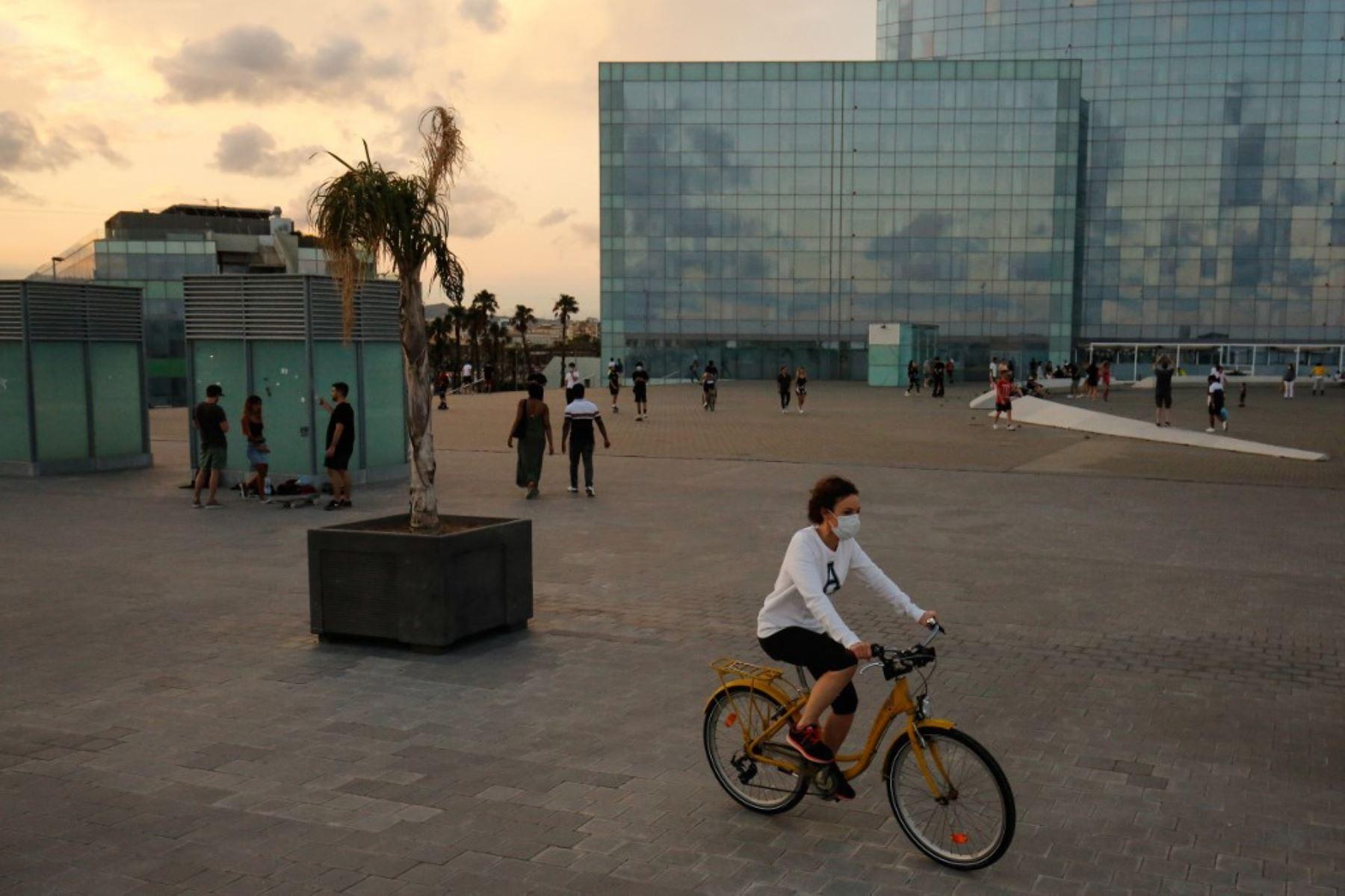 Una mujer monta una bicicleta en el paseo marítimo de la playa de la Barceloneta en Barcelona. Foto: AFP