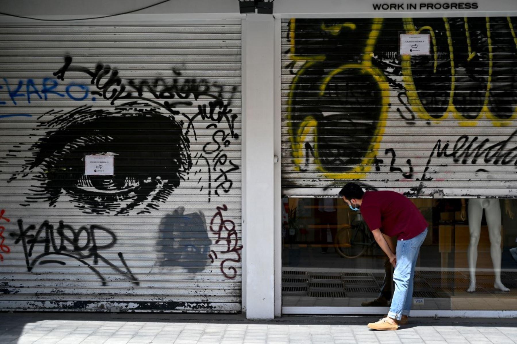 Un hombre comprueba si una tienda de ropa se abrirá ya que la puerta de persiana metálica está medio cerrada, en Madrid. Foto: AFP