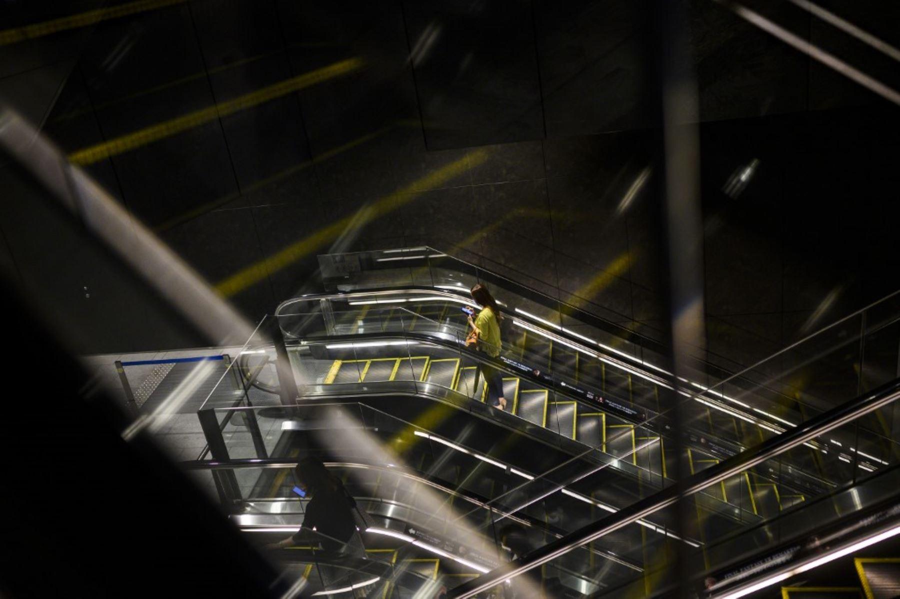 Una mujer que llevaba una máscara facial se sube a una escalera mecánica en el centro comercial Tokyo. Foto: AFP