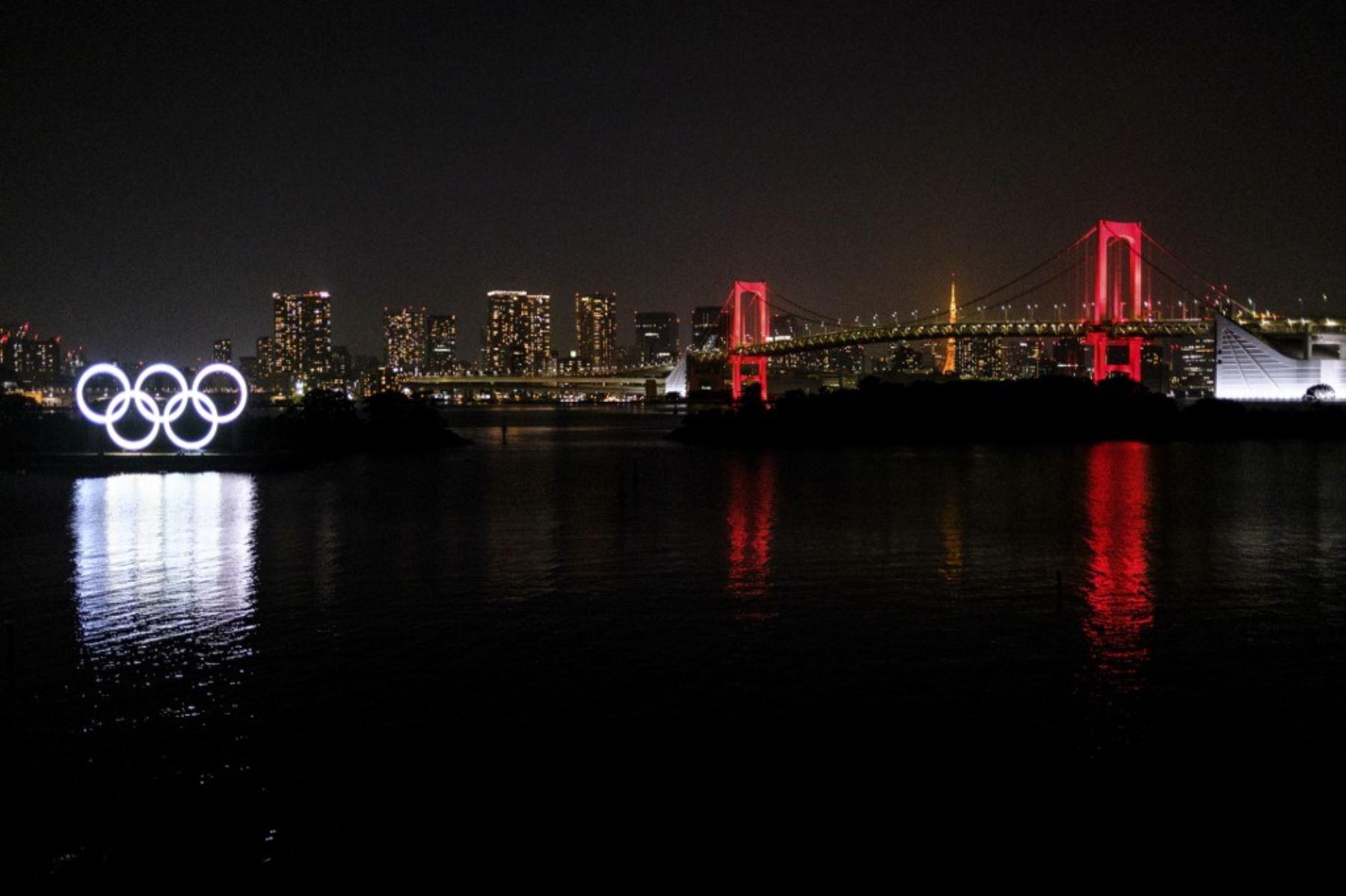 Los anillos olímpicos se ven junto con el Puente del Arco Iris iluminado en rojo por la noche, después de que el gobierno de Tokio decidió emitir una alerta debido a un aumento en los casos de coronavirus COVID-19 en Tokio. Foto: AFP