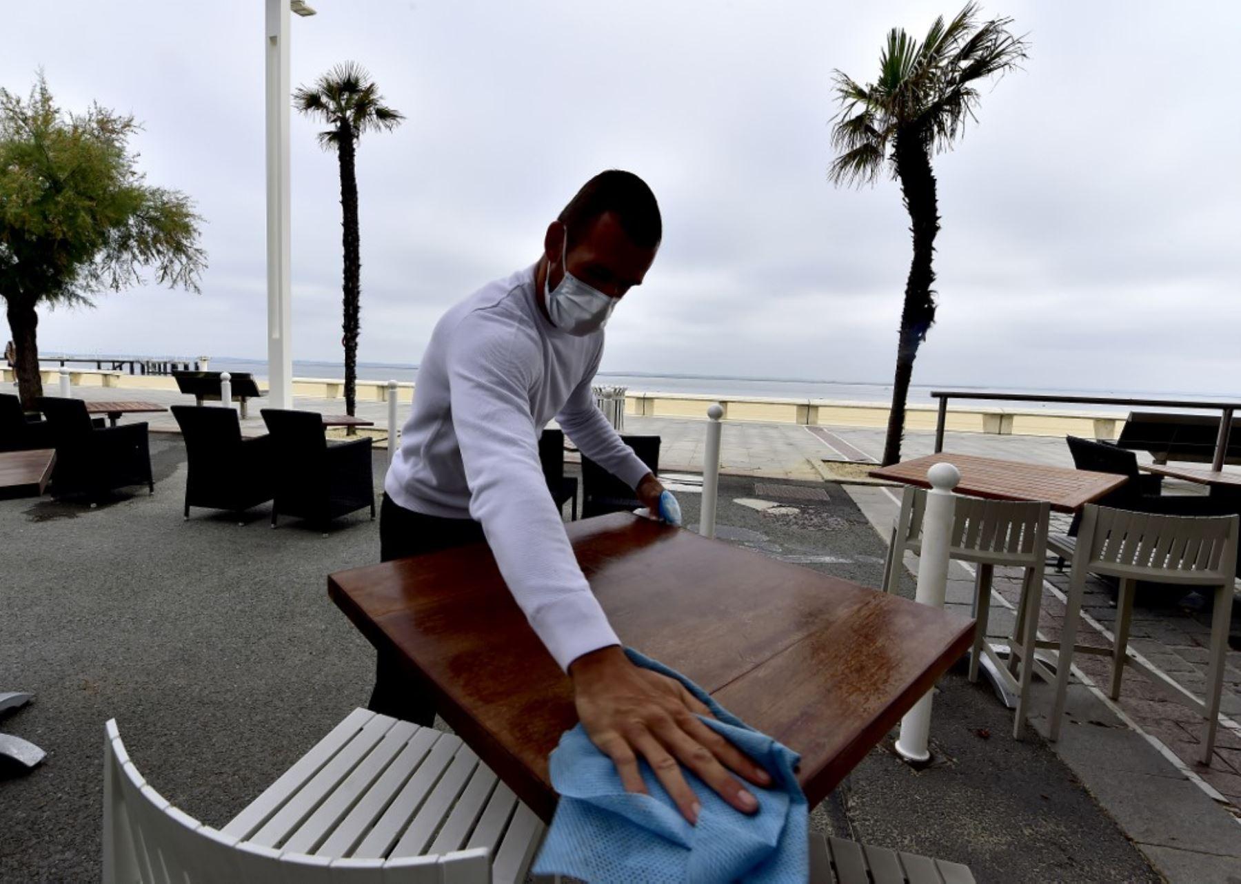 Un camarero con una máscara desinfecta una mesa en una terraza de un restaurante en Arcachon. Foto: AFP