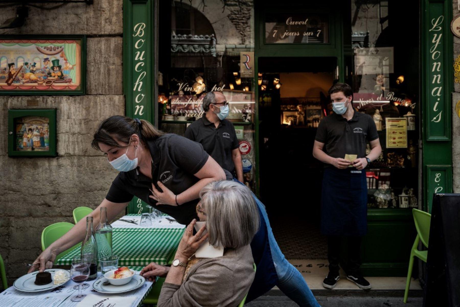 "Un camarero sirve a un cliente en un restaurante local típico conocido como ""Bouchon Lyonnais"". Foto: AFP"