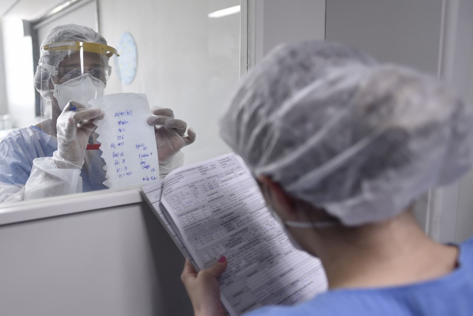 Un profesional de la salud que usa EPP completo  pasa información sobre un paciente COVID-19 a través de una ventana en la Unidad de Cuidados Intensivos (UCI) del hospital Santa Casa en Belo Horizonte, Brasil. Foto: AFP