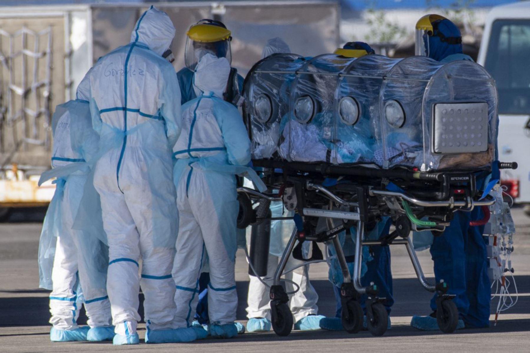 Los trabajadores de salud trasladan a un paciente infectado con COVID-19 a un Hércules C-130, para llevarlo a la ciudad de Concepción, en una base de la Fuerza Aérea de Chile en Santiago. Foto: AFP
