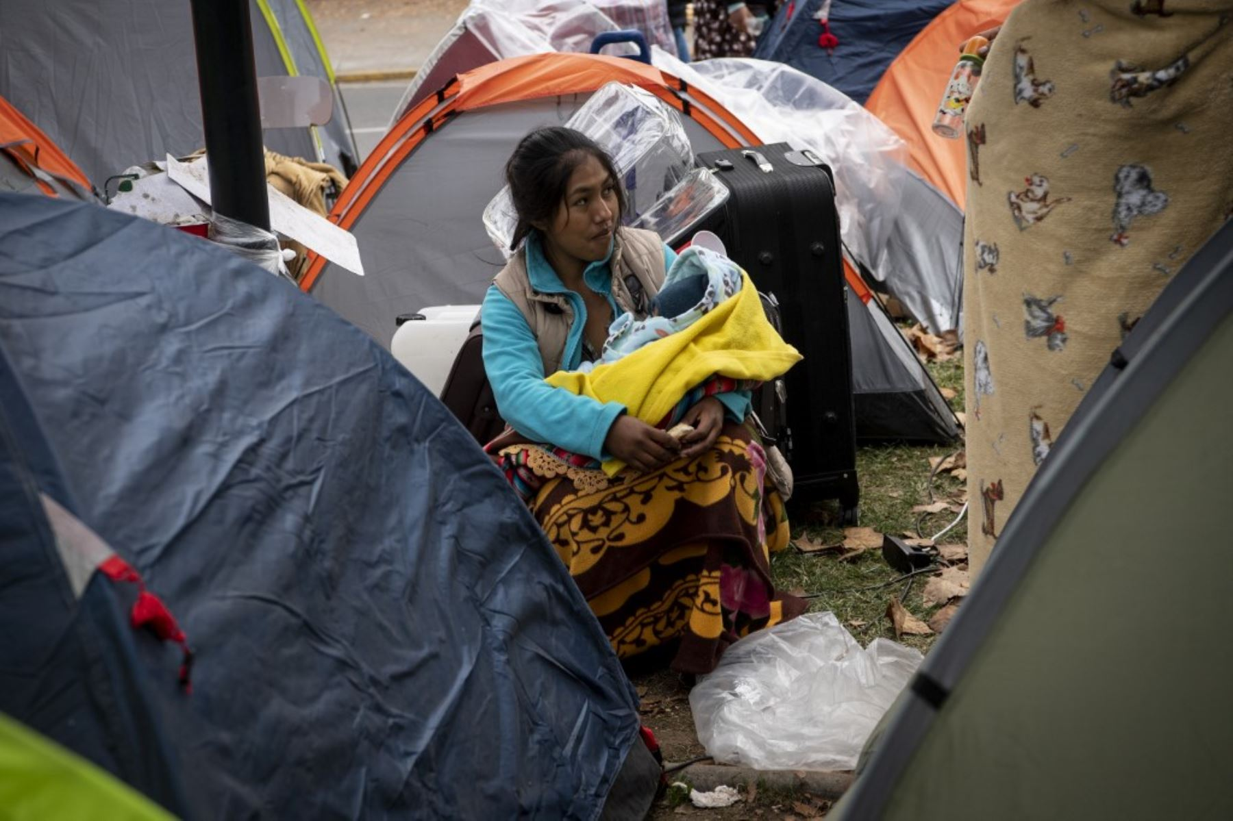 Ciudadanos bolivianos varados permanecen en un campamento improvisado frente al consulado de Bolivia en Santiago de Chile. Foto: AFP