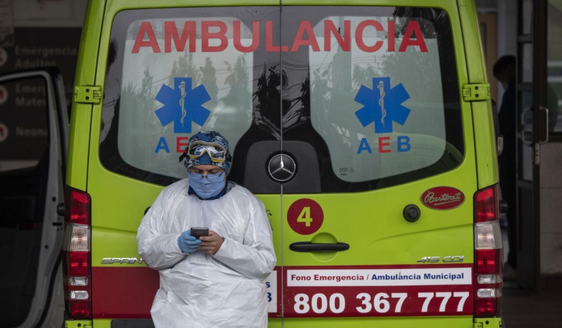 Un trabajador de la salud utiliza su celular junto a una ambulancia que transportaba a un paciente con síntomas del nuevo coronavirus COVID-19, en Santiago de Chile. Foto: AFP