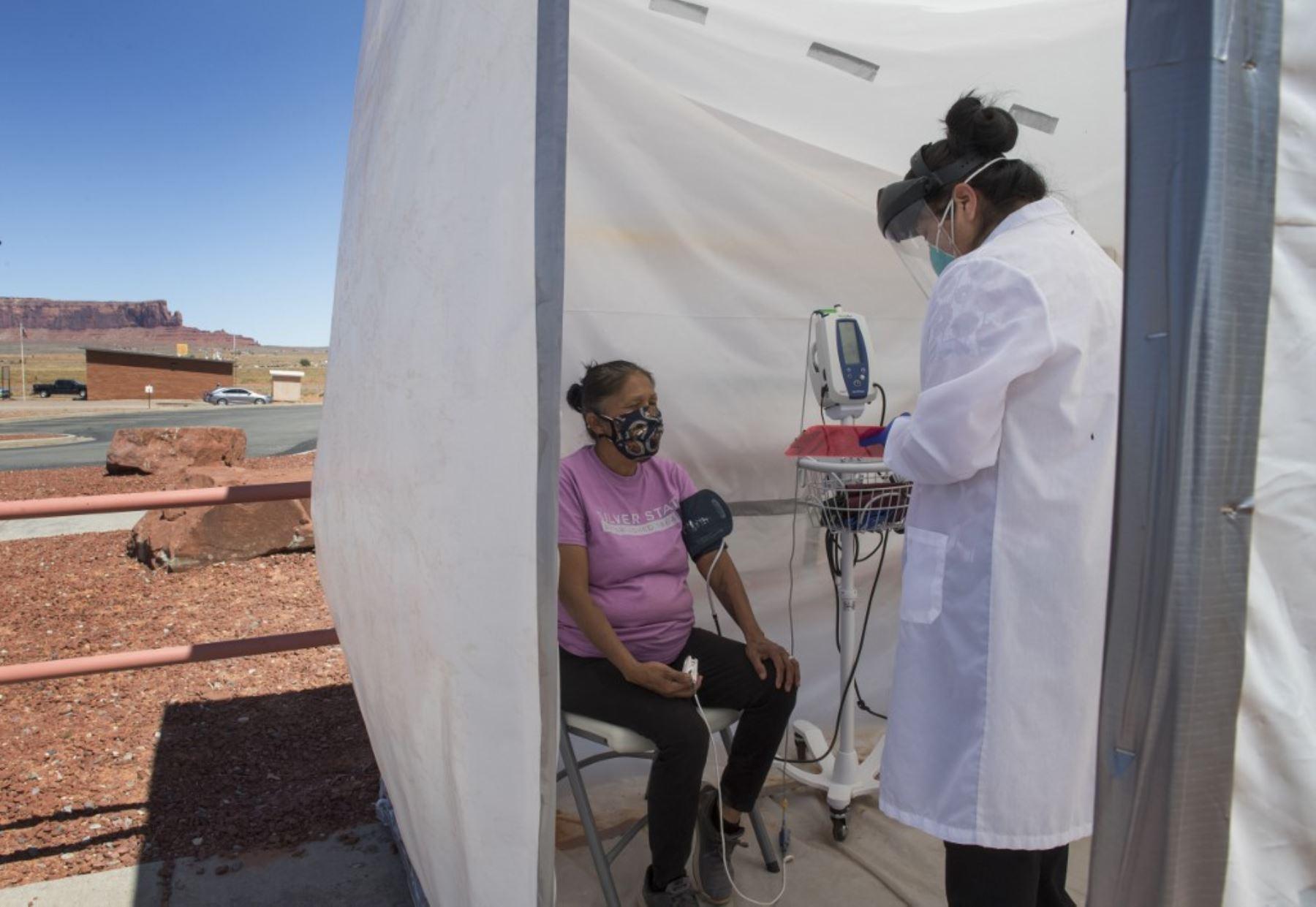 Una enfermera revisa los signos vitales de una mujer indígena navajo que se queja de síntomas de virus, en un centro de pruebas COVID-19 en la ciudad Nación Navajo de Monument Valley en Arizona. Foto: AFP