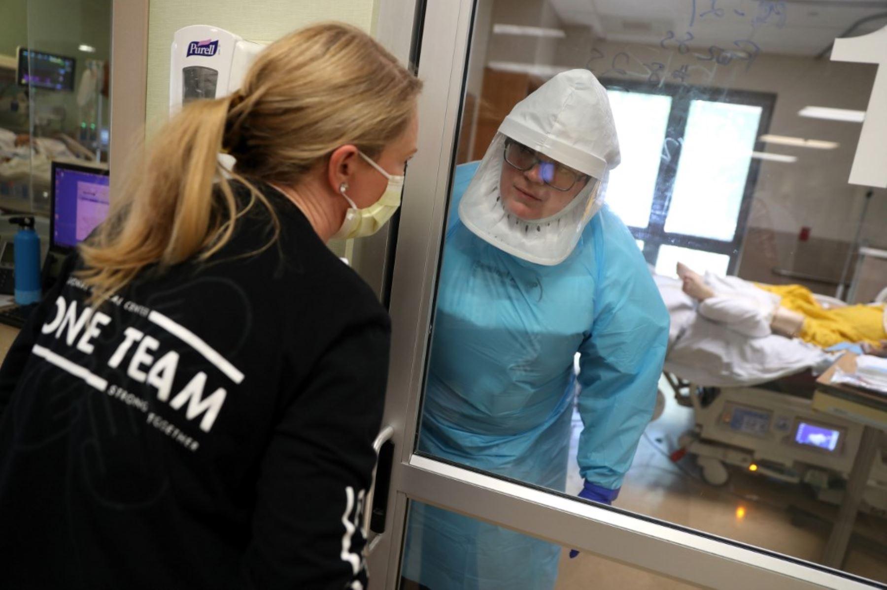 Un médico habla con una enfermera a través de una puerta de vidrio mientras atiende a un paciente con coronavirus COVID-19 en la unidad de cuidados intensivos (UCI) en el Centro Médico Regional en San José, California. Foto: AFP
