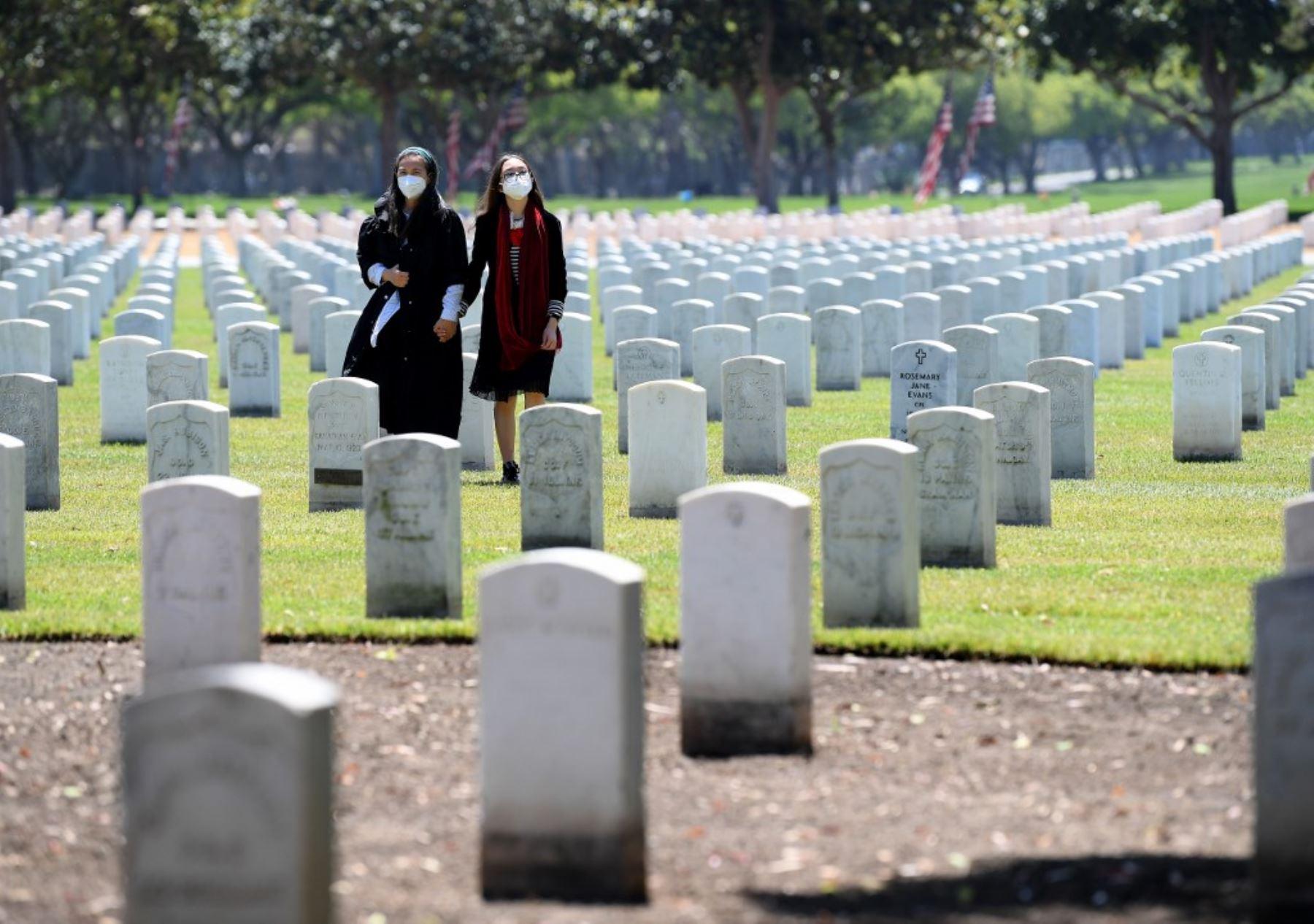 Las personas que usan máscaras protectoras respetan a sus seres queridos en el Día de los Caídos en medio de la pandemia de coronavirus (COVID-19) en el Cementerio Nacional de Los Ángeles. Foto: AFP