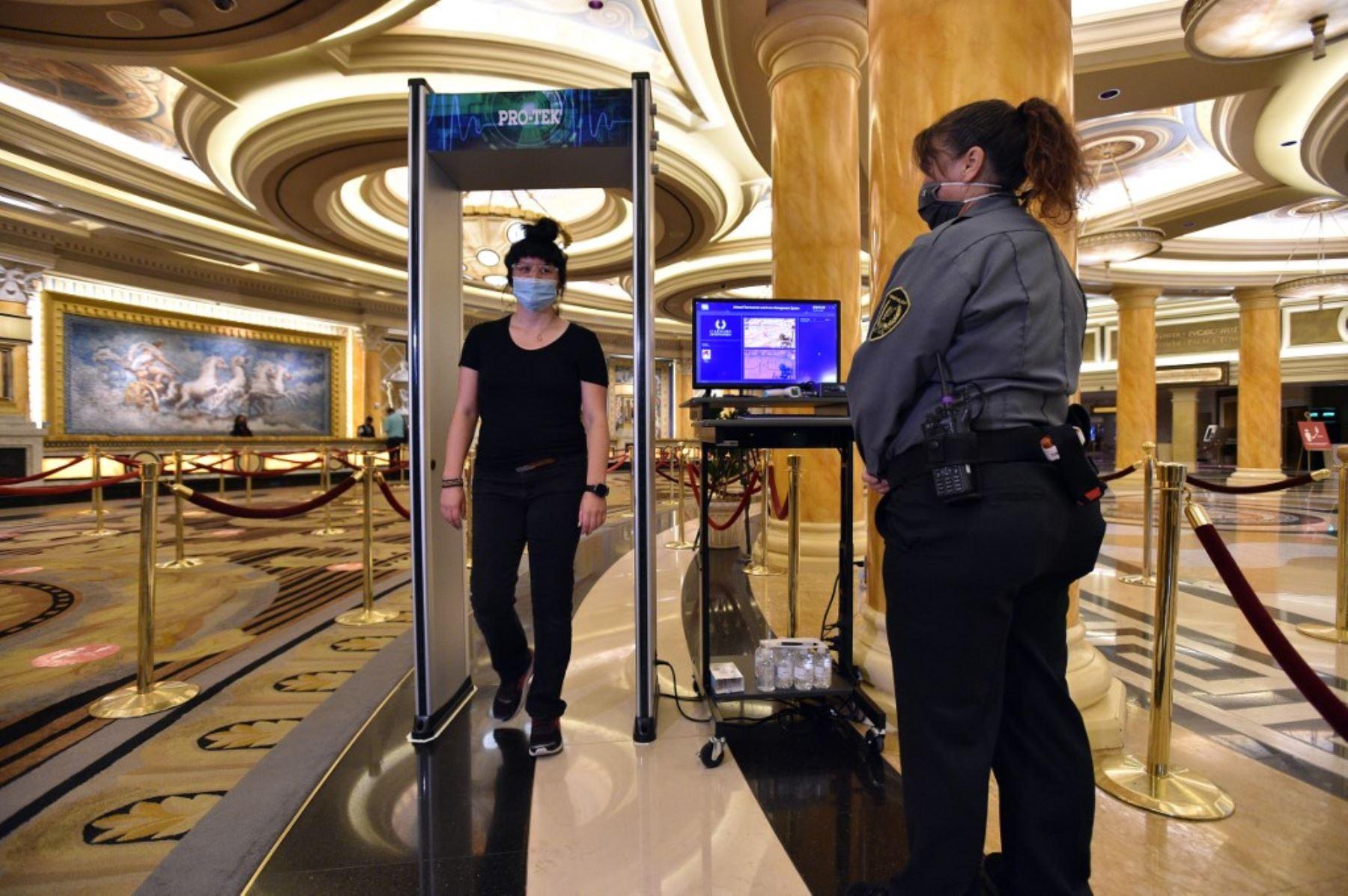 Una mujer pasa a través de un termómetro infrarrojo en el Caesars Palace en Las Vegas Strip, ya que la propiedad abre por primera vez desde que cerró el 17 de marzo debido a la pandemia de coronavirus (COVID-19). Foto: AFP