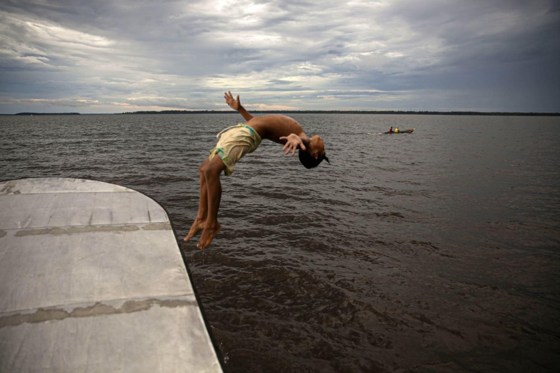 Un niño salta al agua en la bahía de Melgaco, al suroeste de la isla de Marajo, en el estado de Pará, Brasil, en medio de la pandemia de coronavirus. Foto: AFP