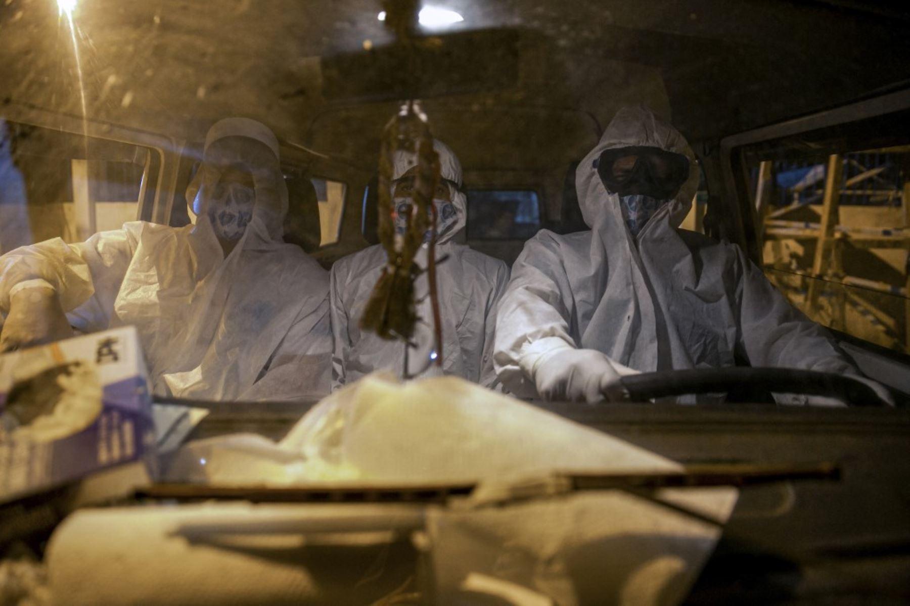 Los sepultureros con ropa protectora llegan al automóvil de una casa funeraria en el cementerio municipal de Recanto da Paz para enterrar a una víctima del nuevo coronavirus COVID-19. Foto: AFP