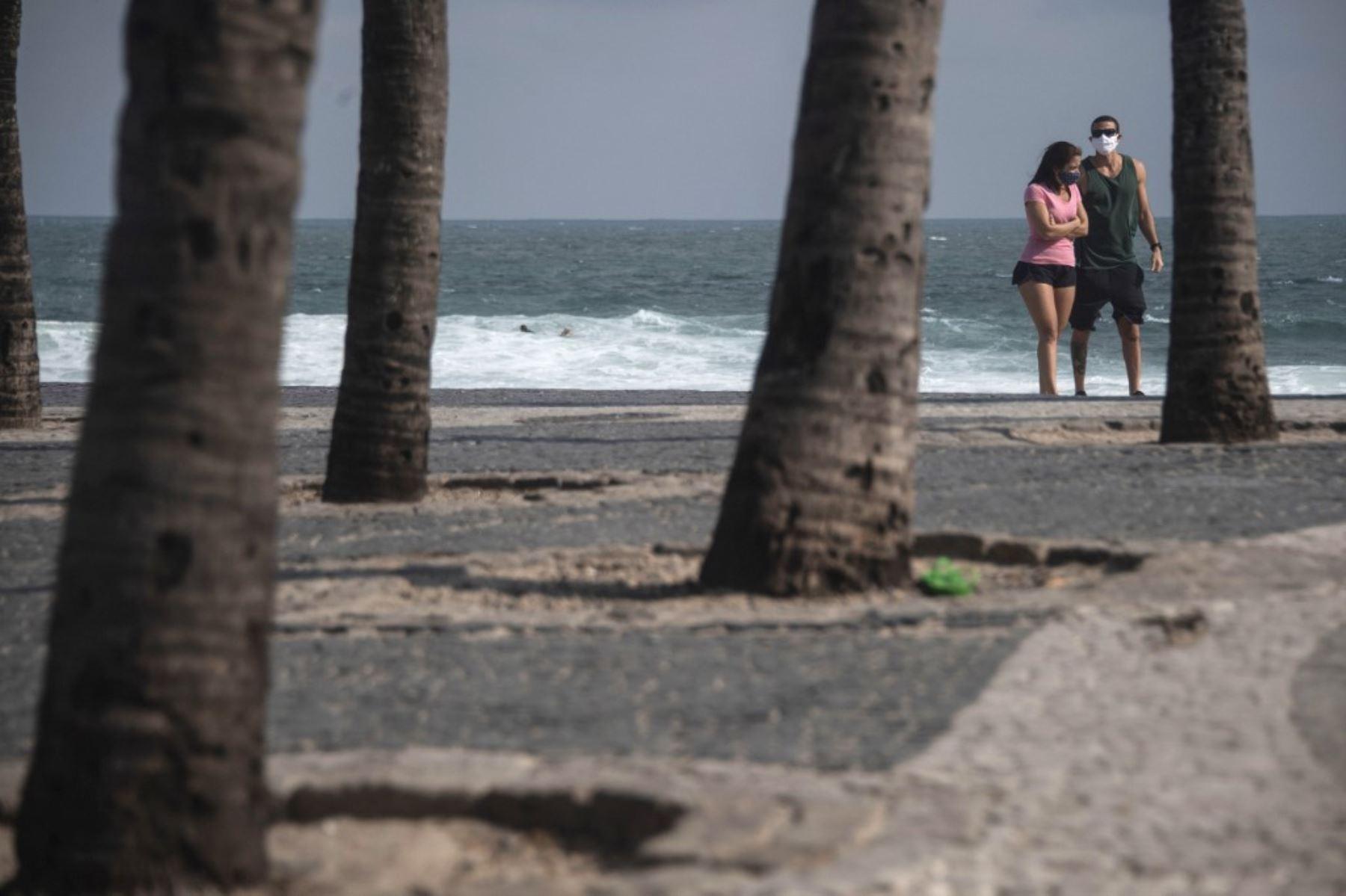 Una pareja con máscara facial caminó en la playa de Arpoador en el estado de Río de Janeiro, Brasil, durante la nueva pandemia de coronavirus COVID-19. Foto: AFP