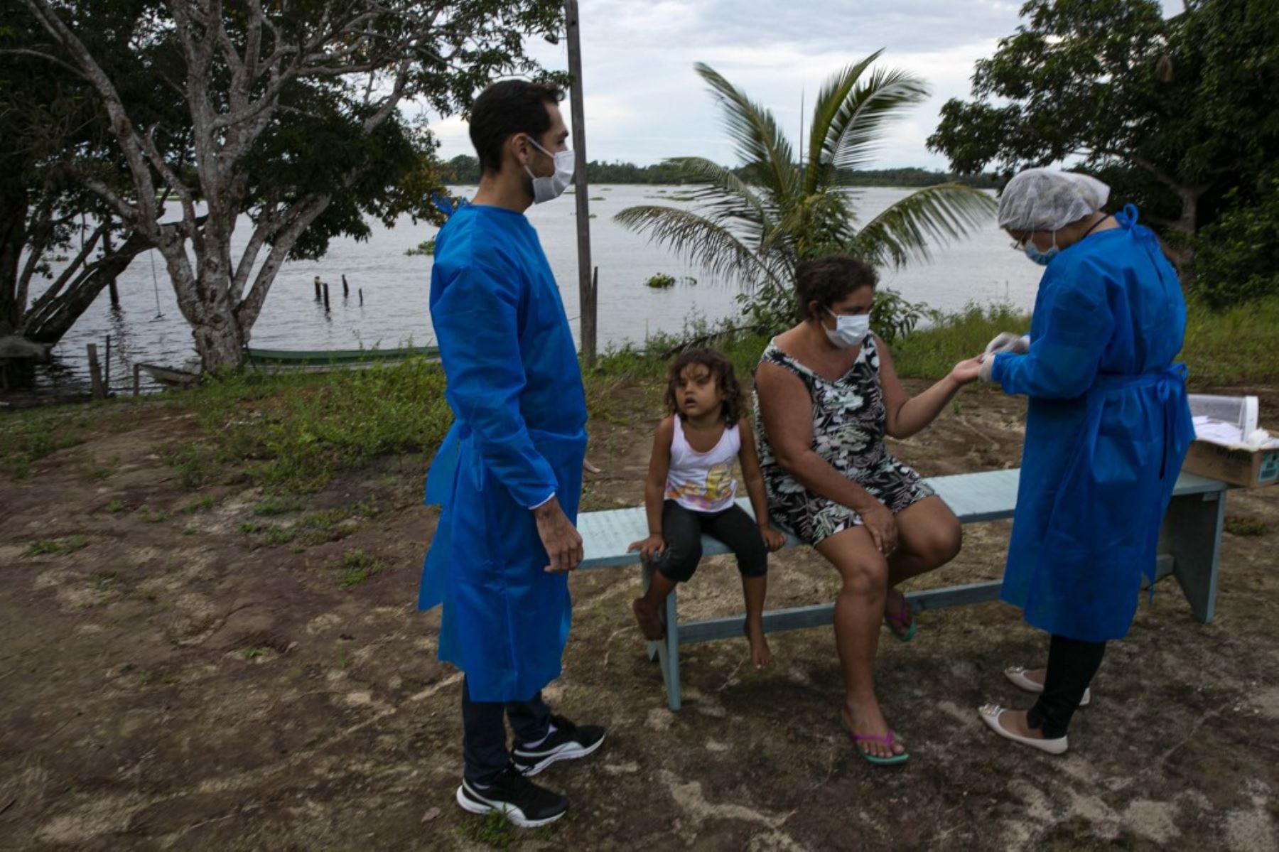 Los trabajadores de salud del gobierno evalúan a un residente de la comunidad ribereña de Roli Madeira en medio de la preocupación por la propagación del coronavirus COVID-19. Foto: AFP