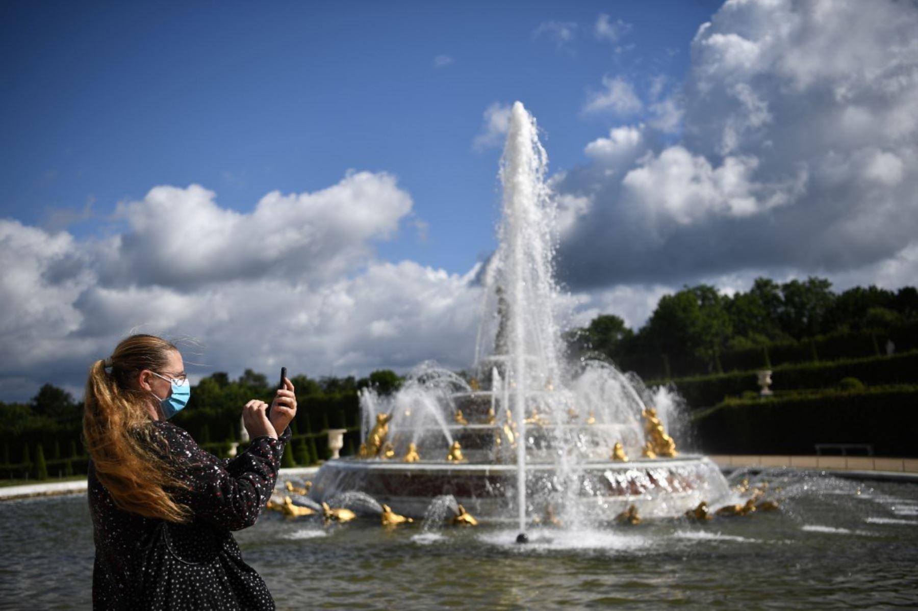 Una mujer usa un teléfono celular mientras visita el parque del histórico castillo francés de Versalles. Foto: AFP