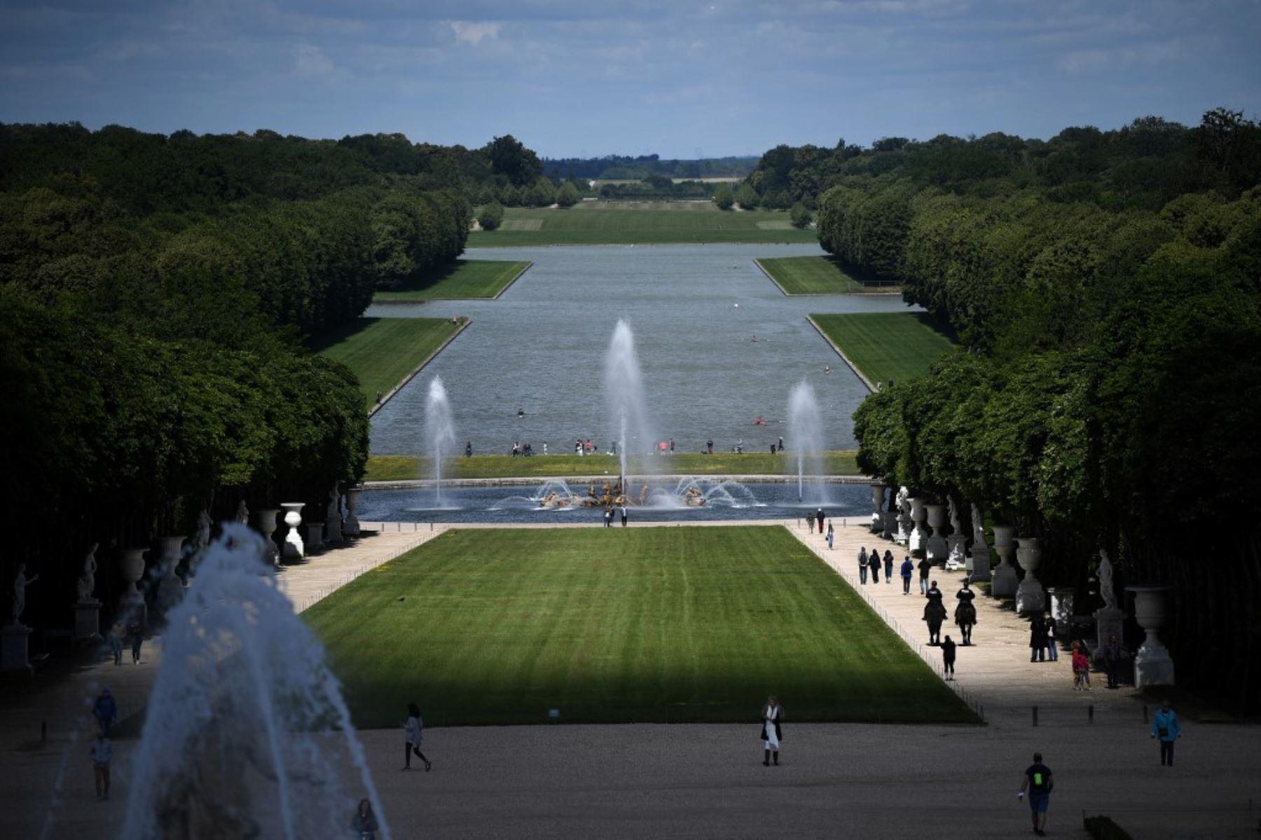Un buen grupo de personas transita en el parque del histórico Palacio de Versalles, cerca de París, Francia. Foto: AFP