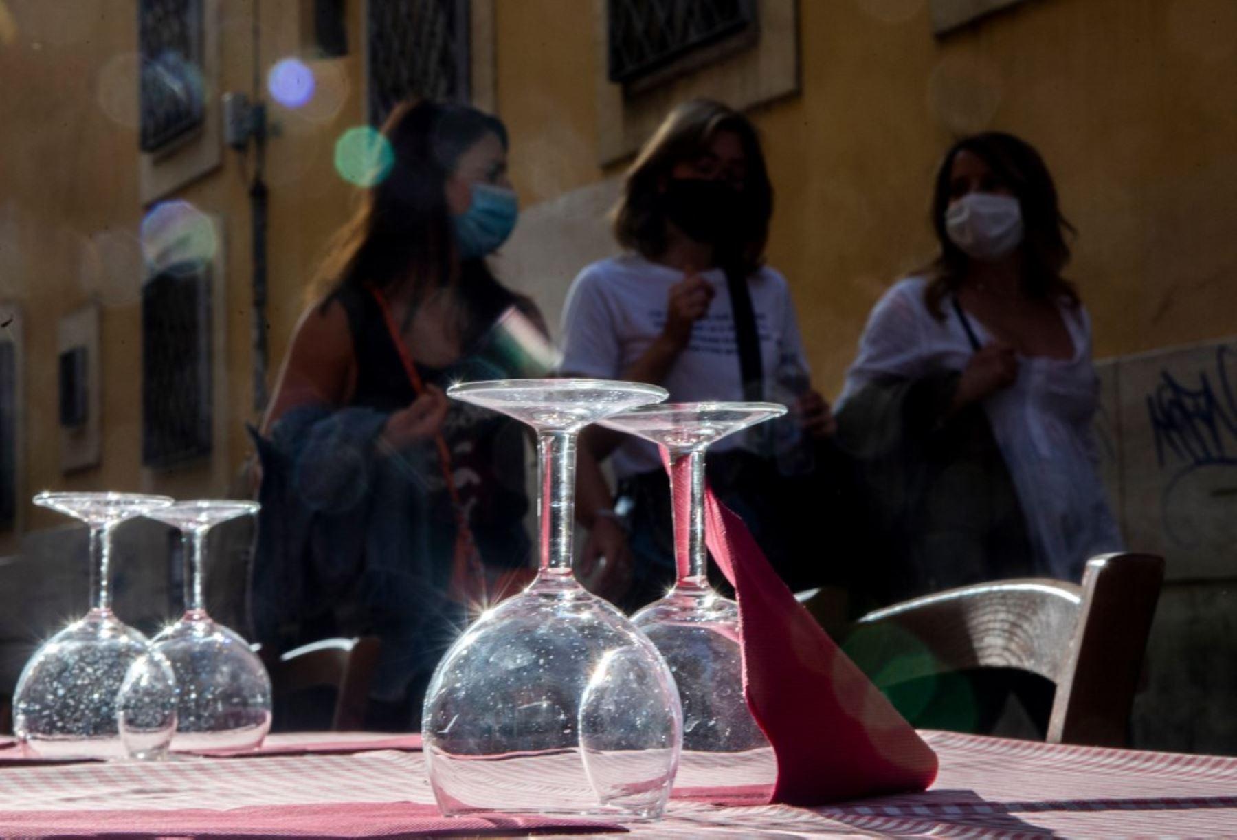 Un grupo de mujeres que llevan máscaras protectoras pasan junto a la terraza de un restaurante en Trastevere, en el centro de Roma. Foto: AFP
