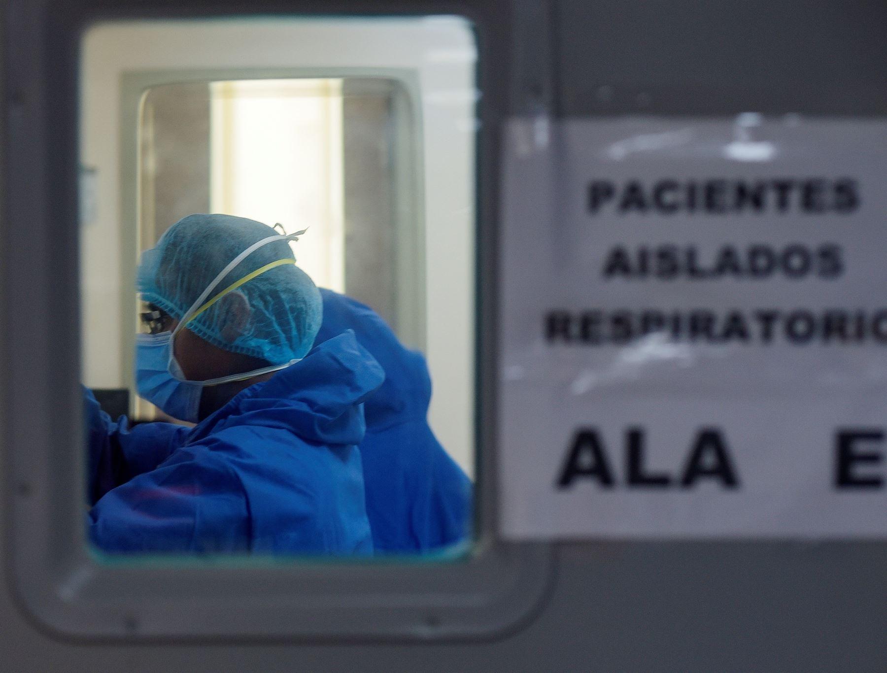 """Fotografía de un médico de la Unidad de Cuidados Intensivos (UCI) del hospital """"Los Ceibos"""", de la ciudad portuaria de Guayaquil, que pasa revista a una paciente contagiada covid-19. Foto: EFE"""