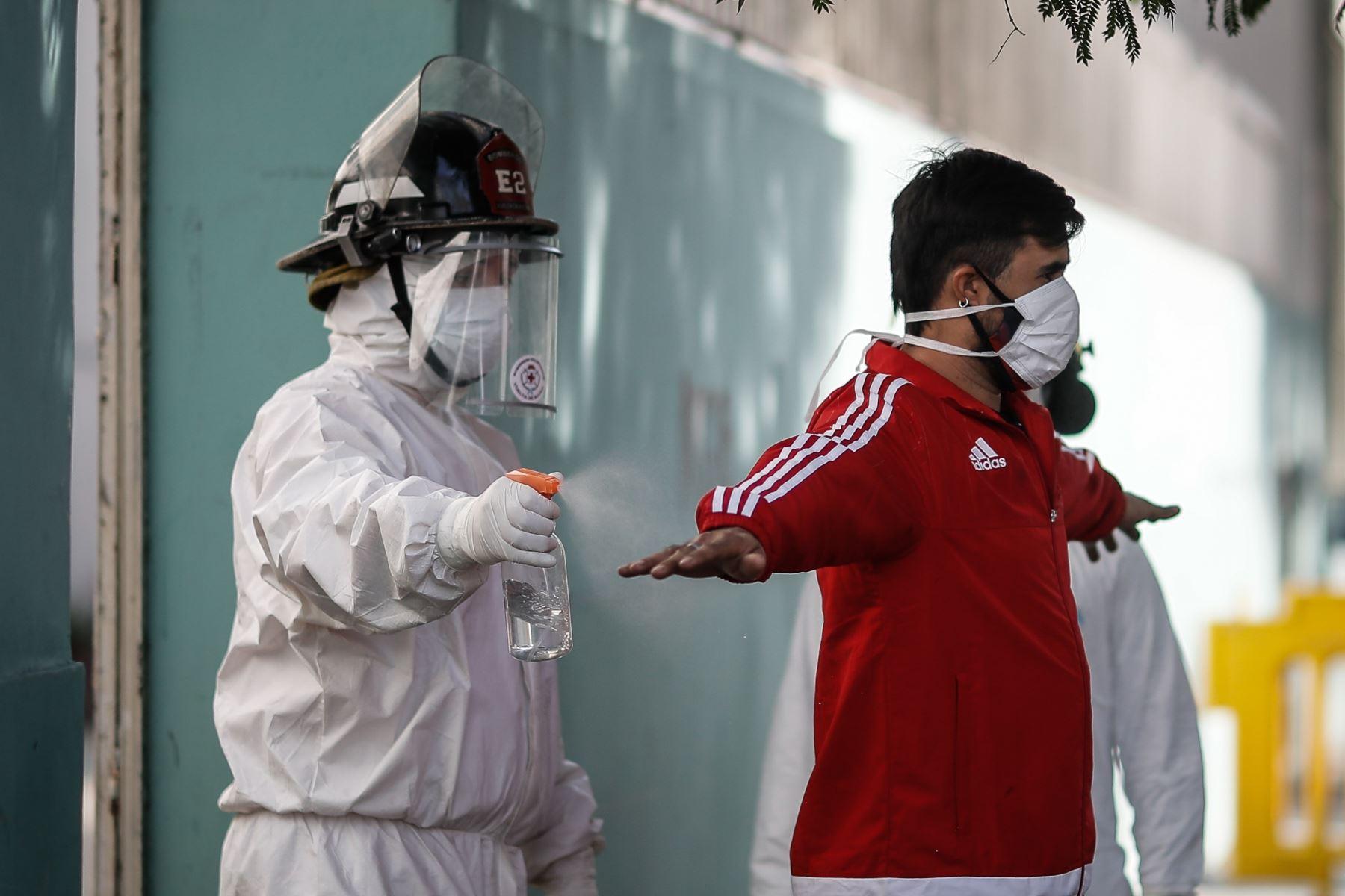 Un bombero rocía con alcohol a un hombre durante una jornada de tomas de pruebas de coronavirus este martes, en el barrio Constitución de Buenos Aires (Argentina). Foto: EFE