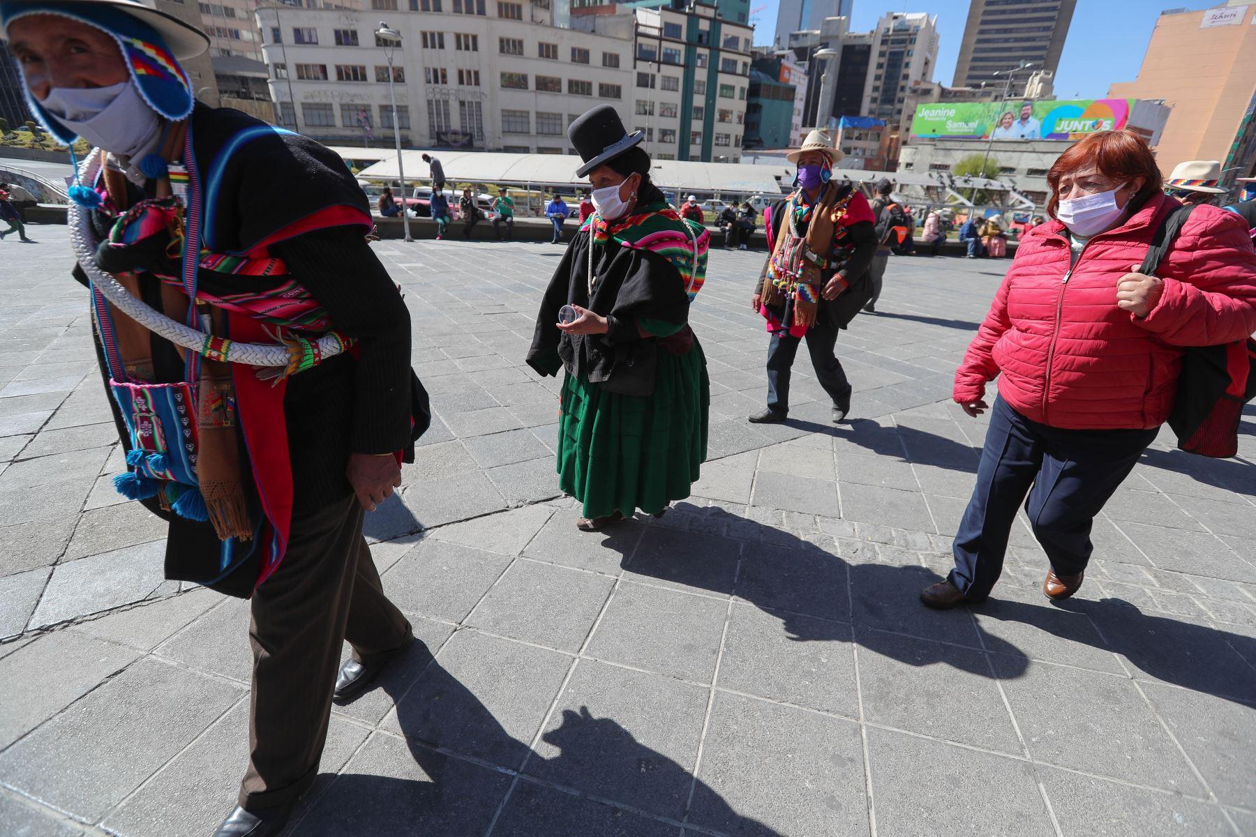 Indígenas aymaras caminan en una plaza este jueves, a tres meses de la cuarentena decretada por la pandemia de covid-19, en La Paz (Bolivia). Foto: EFE