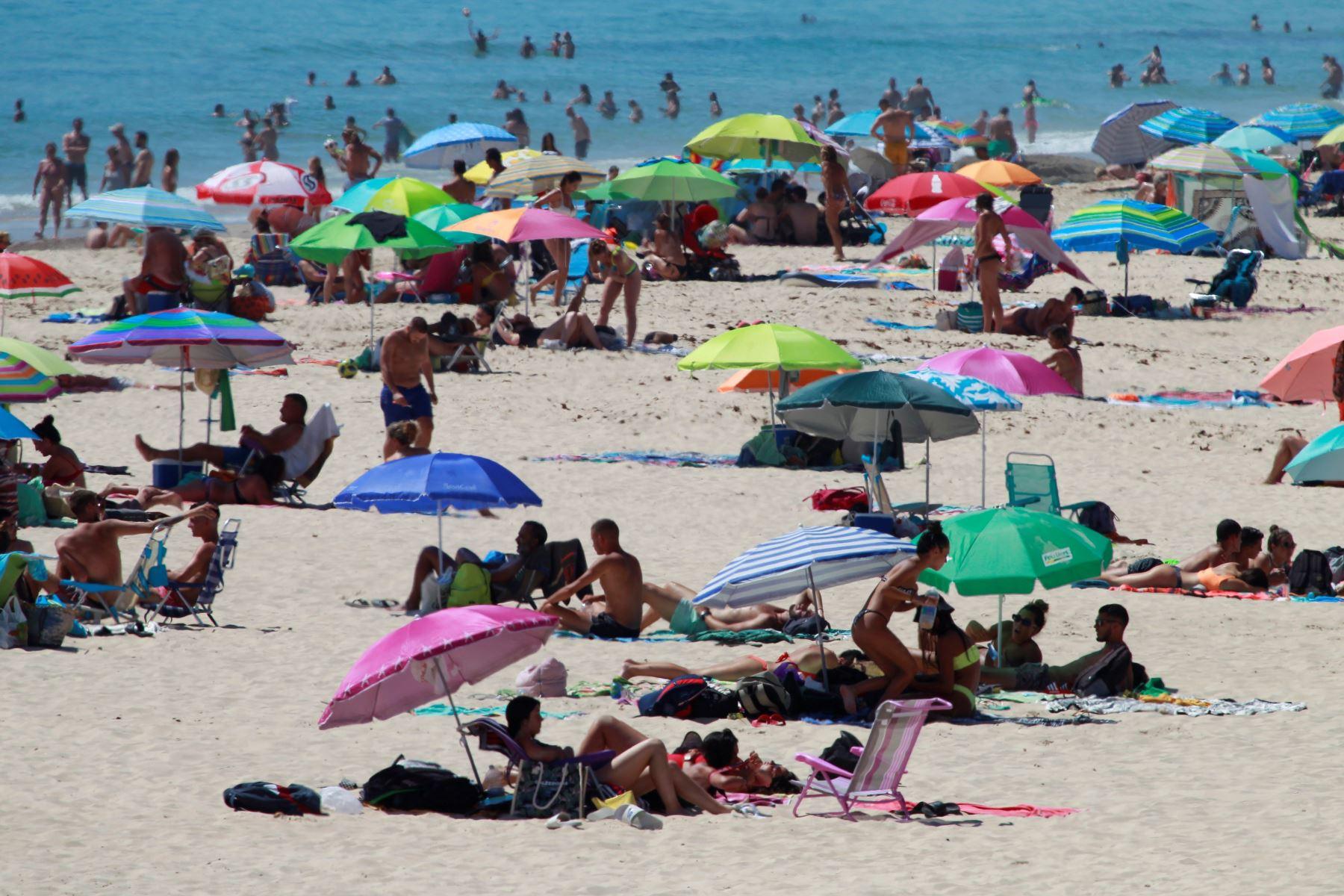 Decenas de personas disfrutan de un soleado día en la playa de Los Lances, en Tarifa (Cádiz), este domingo, primer fin de semana de la