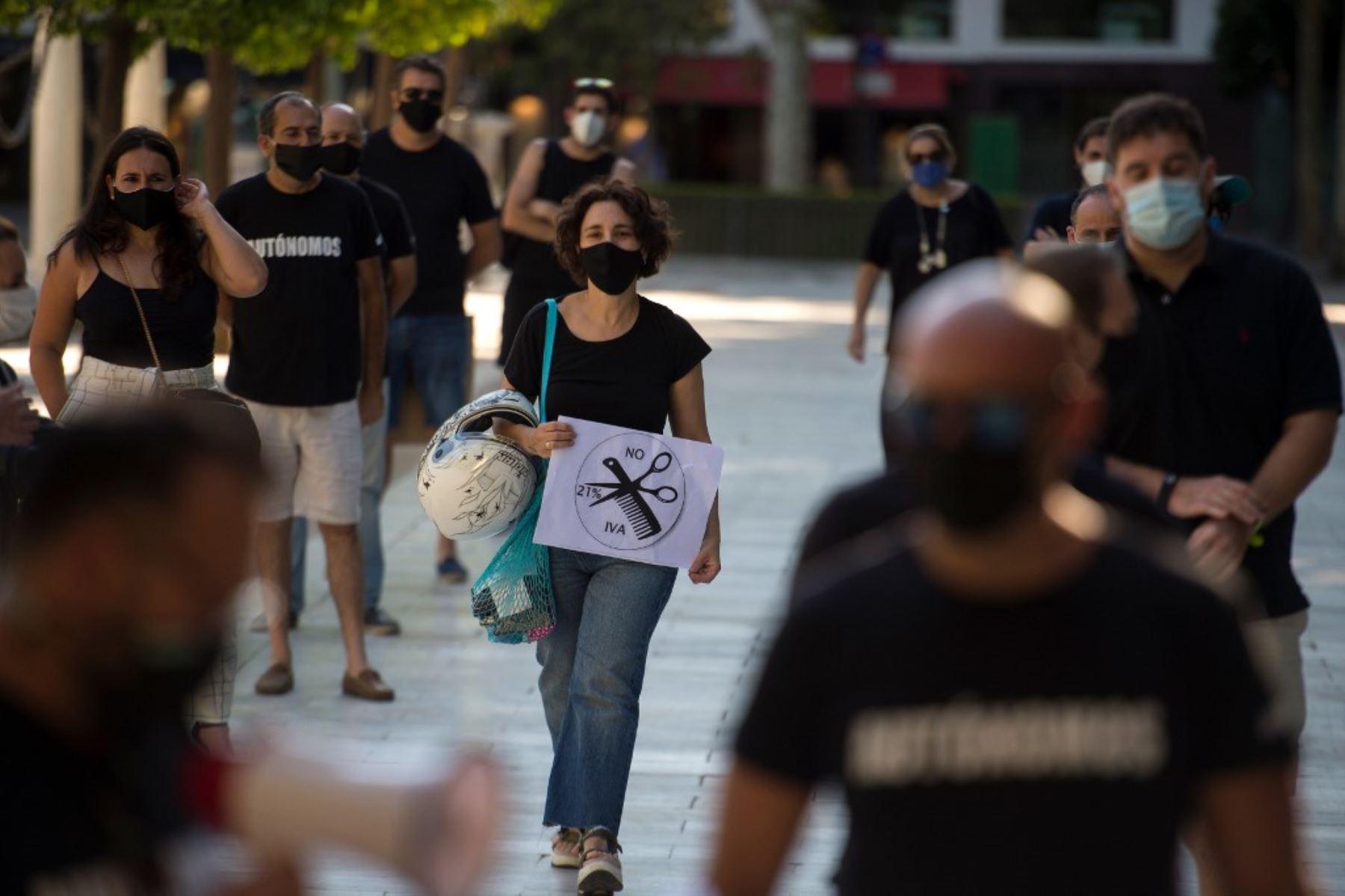 Los trabajadores independientes que usan máscaras faciales, en Sevilla. Foto: AFP