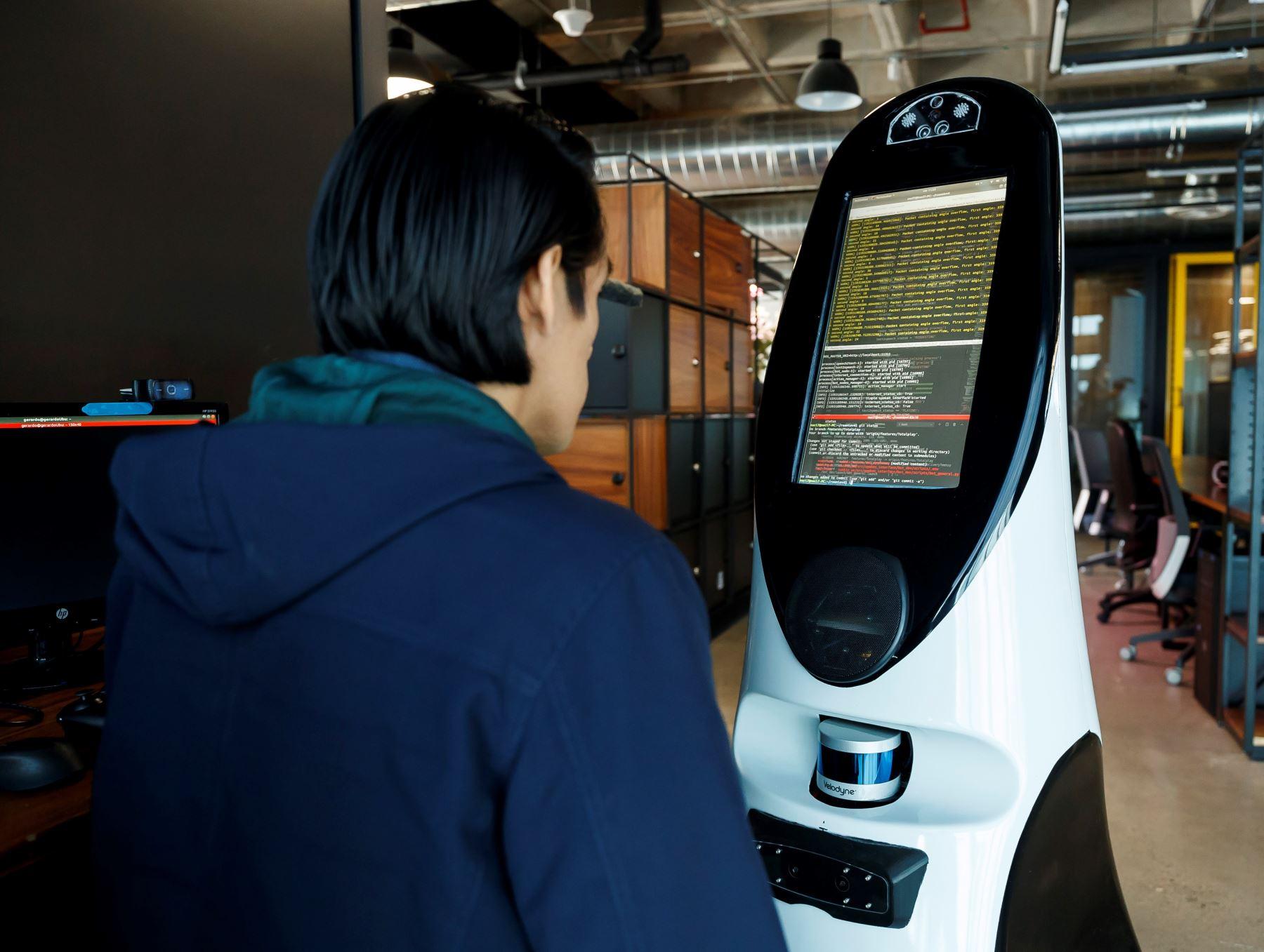 Fotografía con fecha del 26 de junio, de un integrante de la empresa CEO de Roomie, programando uno de los robots de asistencia para la detección de Covid-19 en Ciudad de México (México). Foto: EFE