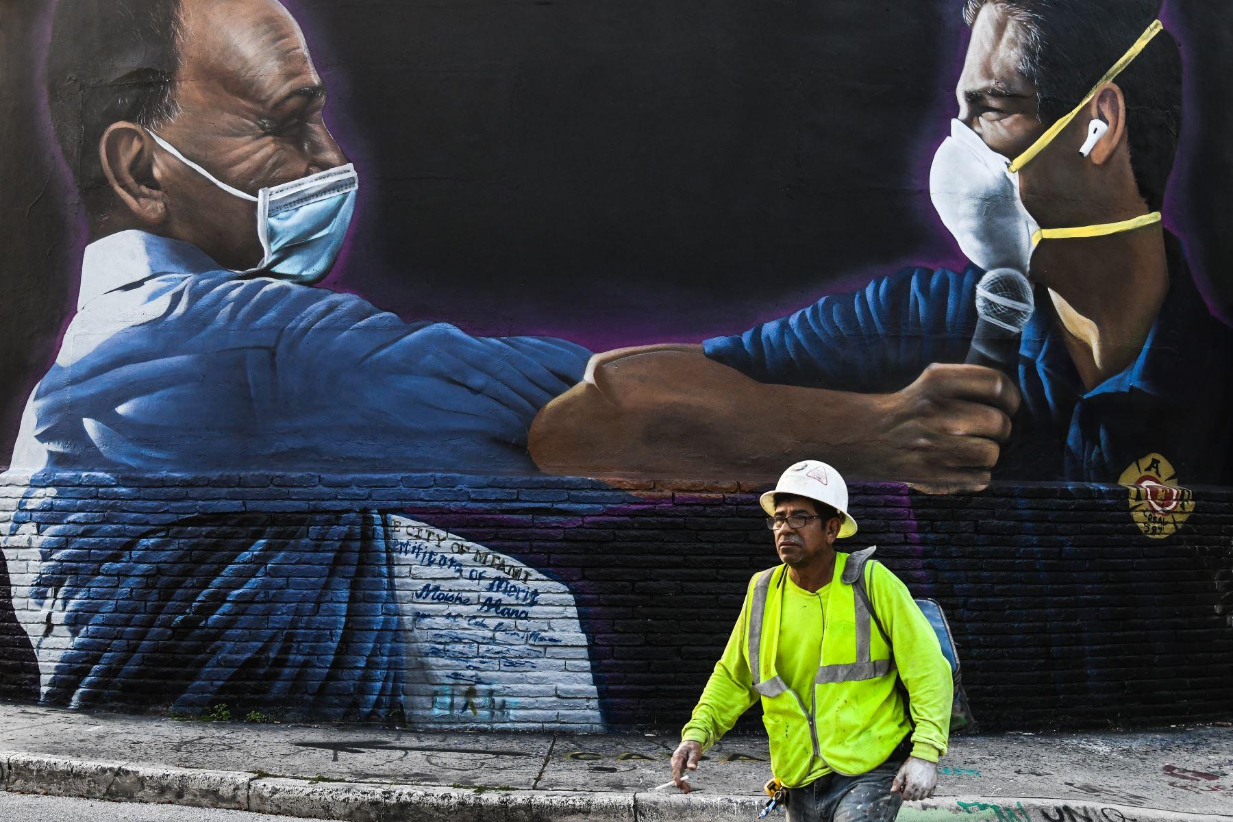 Un trabajador de construcción pasa junto a un mural sobre el coronavirus en el distrito artístico de Wynwood en Miami, Florida. Foto: AFP