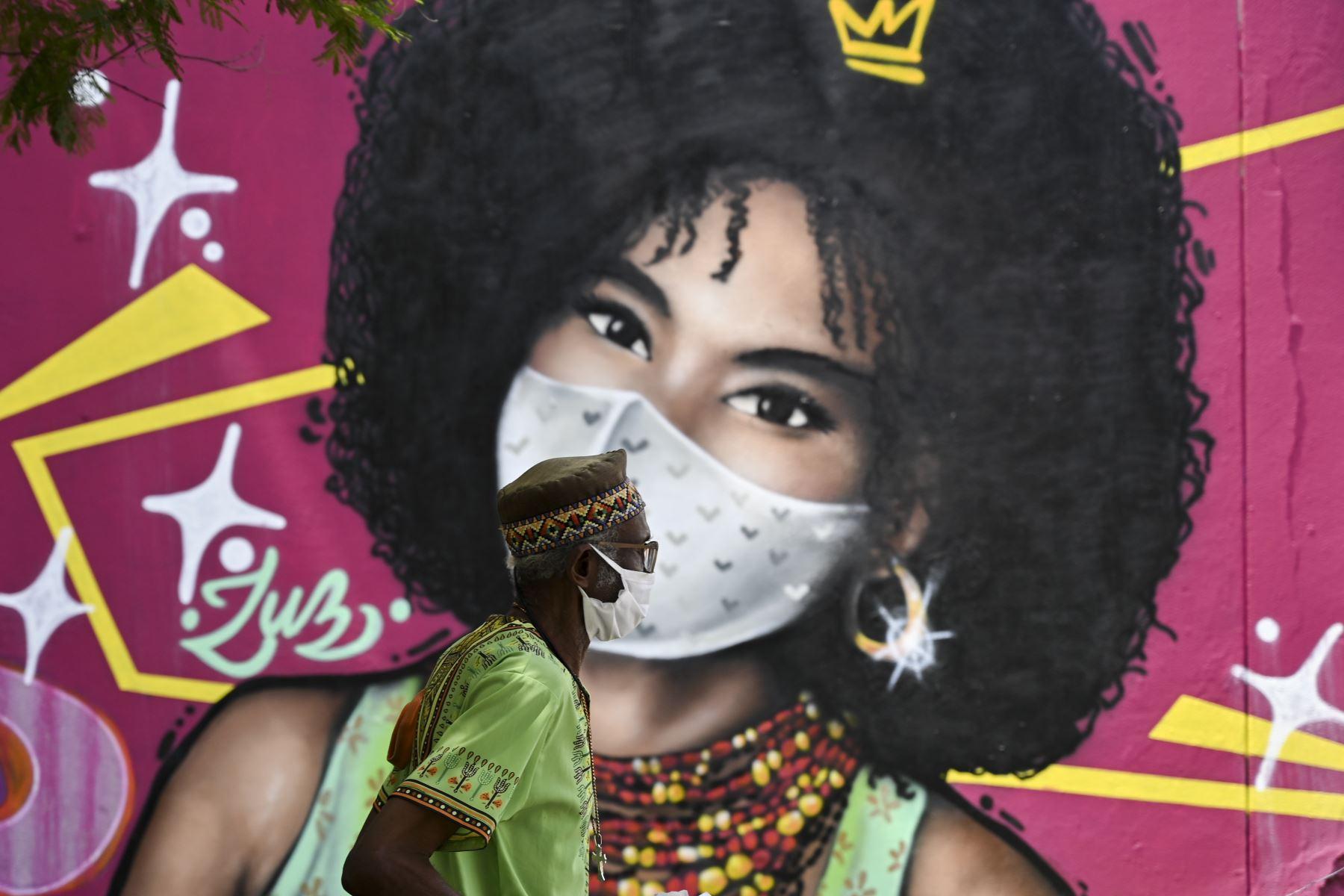Un hombre usa una máscara facial como medida preventiva contra la propagación del nuevo coronavirus cuando pasa junto a un mural en Cali, Colombia. Foto: AFP