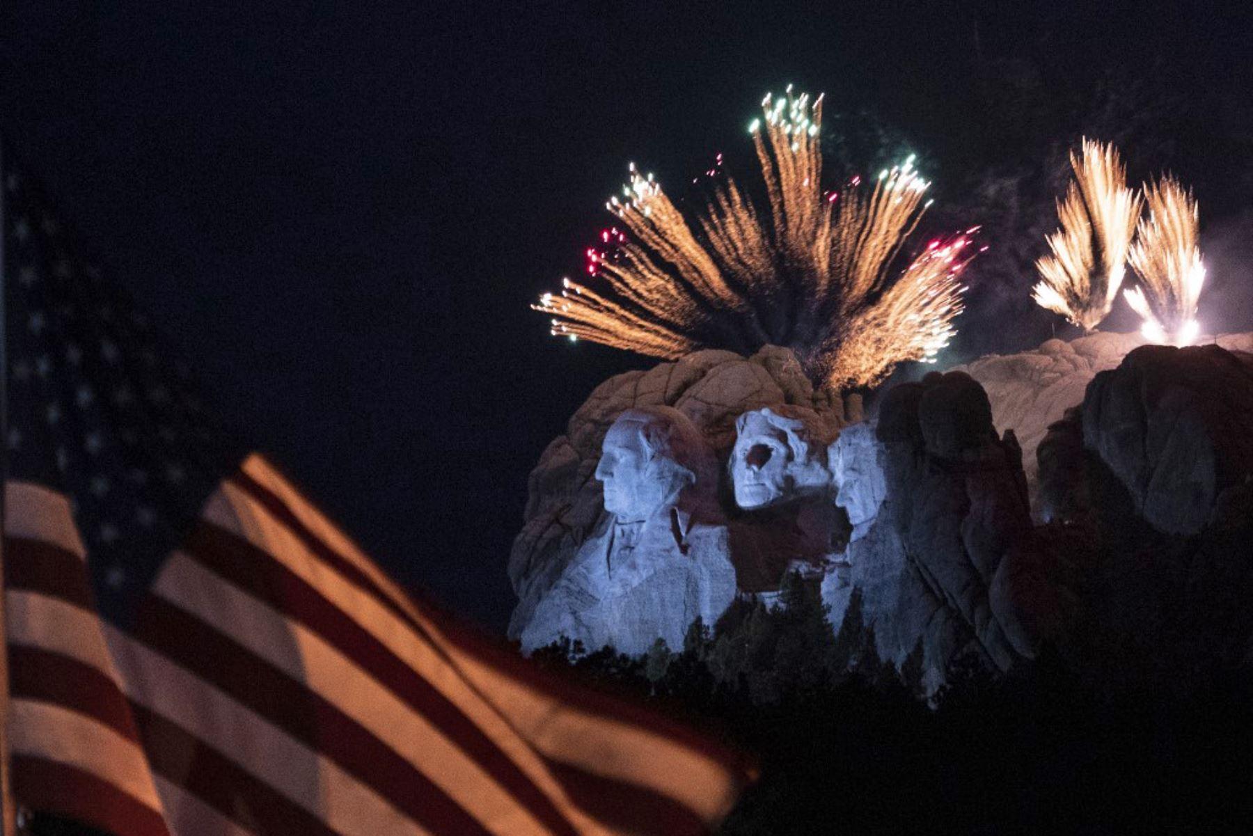 Una bandera de los Estados Unidos ondea mientras los fuegos artificiales explotan sobre el Monumento Nacional del Monte Rushmore durante un evento del Día de la Independencia al que asistió el presidente de los Estados Unidos en Keystone, Dakota del Sur. Foto: AFP