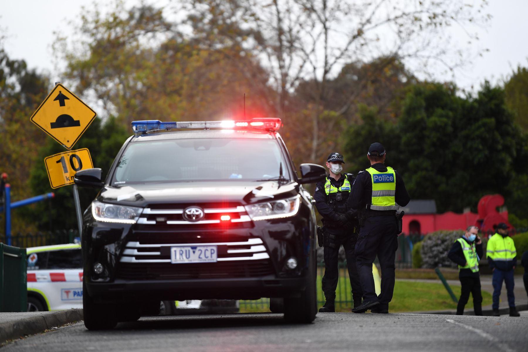 Agentes de la Policía de Victoria vigilan en las afueras de una torre de viviendas públicas en Racecourse Road en Melbourne, Australia, después de que se decretara el cierre inmediato de nueve torres en Flemington y North Melbourne tras registrarse un brote de coronavirus. Foto: EFE