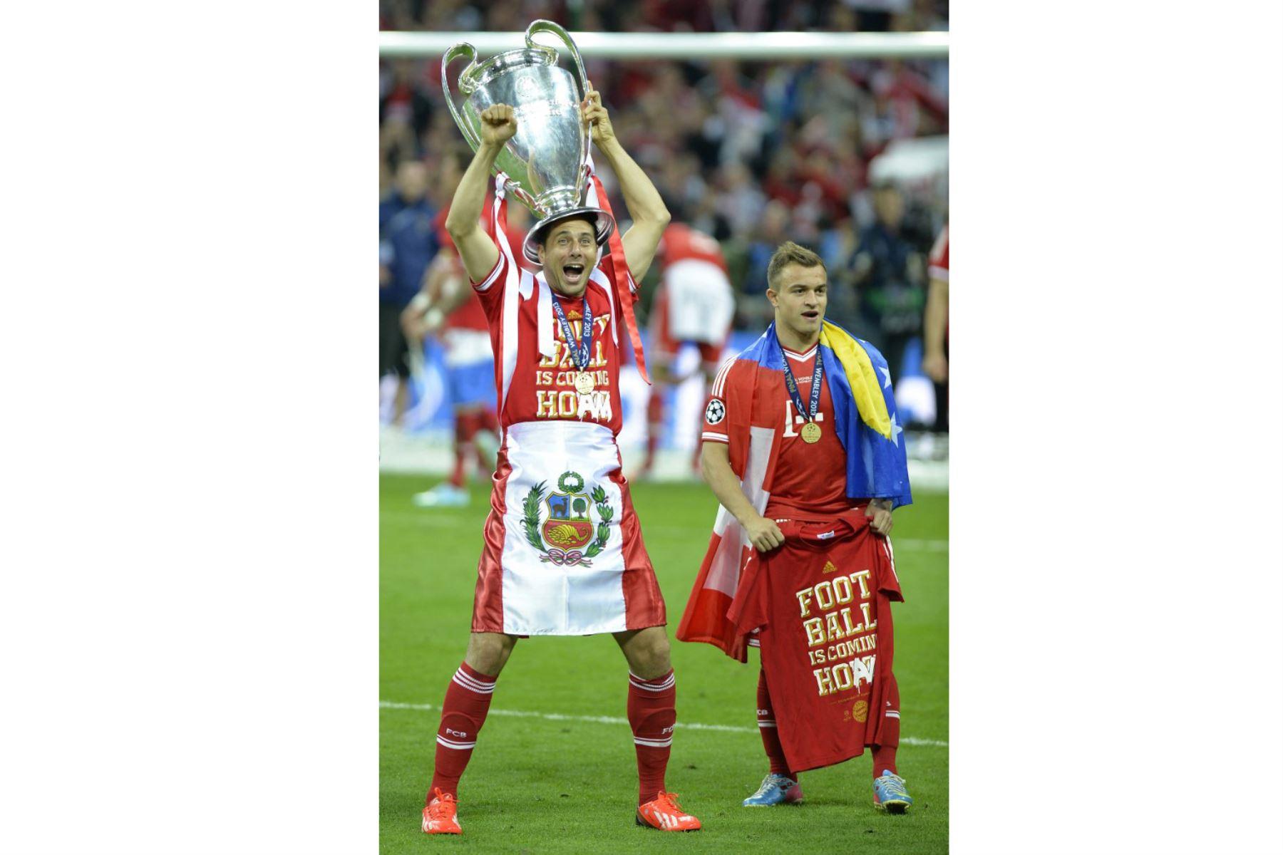 El delantero peruano del Bayern Munich Claudio Pizarro  celebra con el trofeo en el campo después de su victoria en el partido de fútbol final de la UEFA Champions League entre el Borussia Dortmund y el Bayern Munich en el estadio de Wembley en Londres. Foto: AFP