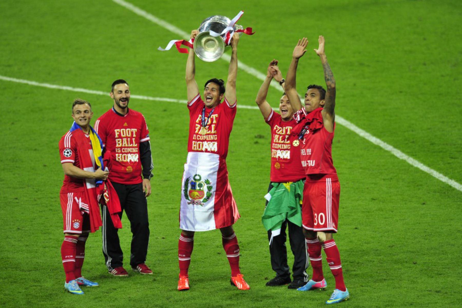 El delantero peruano del Bayern Munich Claudio Pizarro  celebra con el trofeo en el campo con sus compañeros de equipo después de su victoria en el partido de fútbol final de la UEFA Champions League entre el Borussia Dortmund y el Bayern Munich en el estadio de Wembley en Londres. Foto: AFP