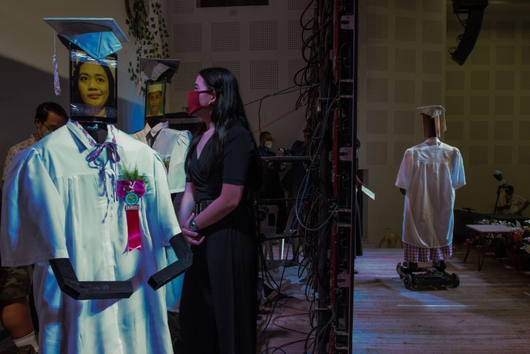 """Los robots, con las imágenes de los estudiantes graduados que se muestran en tabletas, se alinean para subir al escenario mientras se lleva a cabo la primera ceremonia de """"graduación cibernética"""" de una universidad de ciencia y tecnología debido a la prohibición de reuniones masivas durante el brote de coronavirus COVID-19 en Manila, Filipinas. Foto: AFP"""