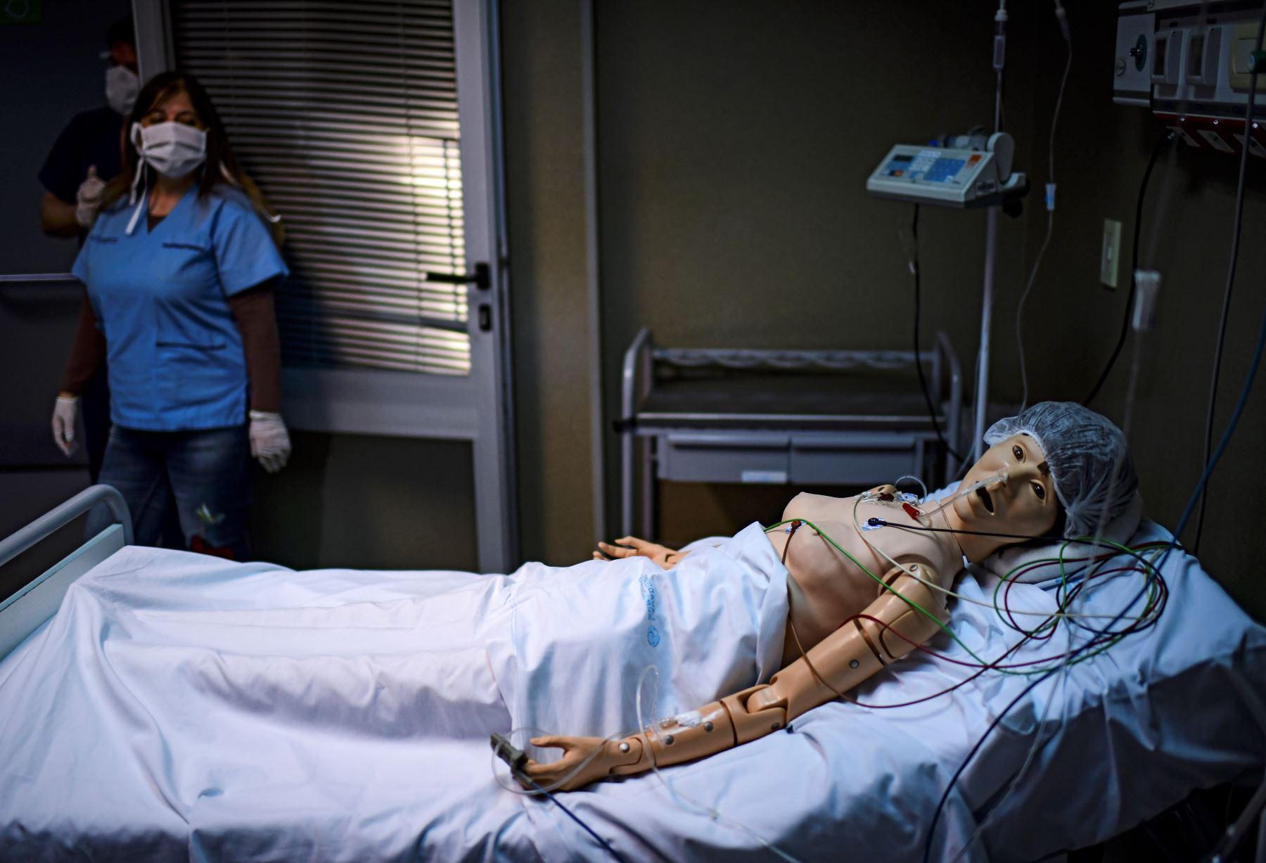 La doctora Norma Raul mira un robot con el que practica asistencia médica para pacientes con COVID-19, en el Centro de Entrenamiento de Simulación Clínica del hospital El Cruce en Buenos Aires, Argentina. Foto: AFP