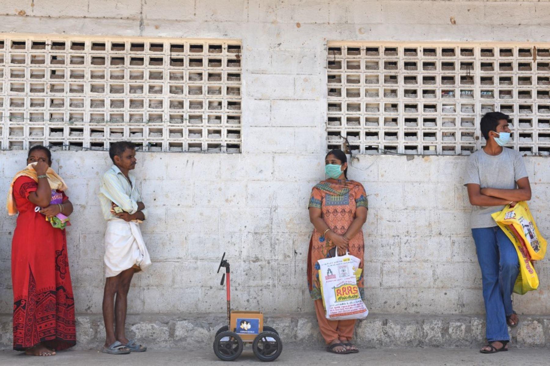 El ingeniero indio Karthik Velayutham usa su robot en una cola para esperar su turno fuera de una tienda de raciones en Coimbatore. Foto: AFP