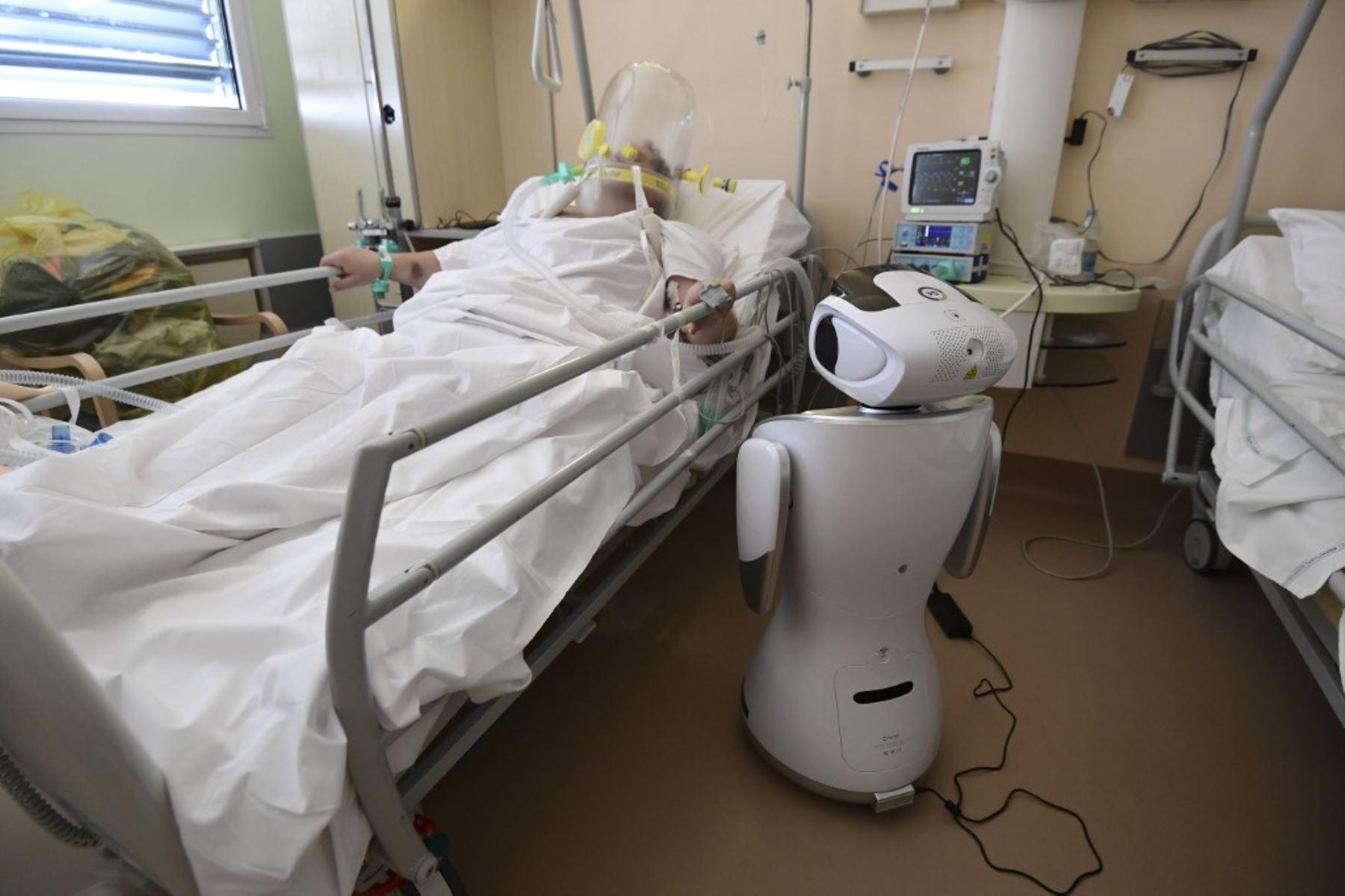 Uno de los seis robots del hospital Circolo di Varese se encuentran cerca de un paciente para ayudar al personal de atención médica del departamento de Medicina de Alta Intensidad, en Italia. Foto: AFP