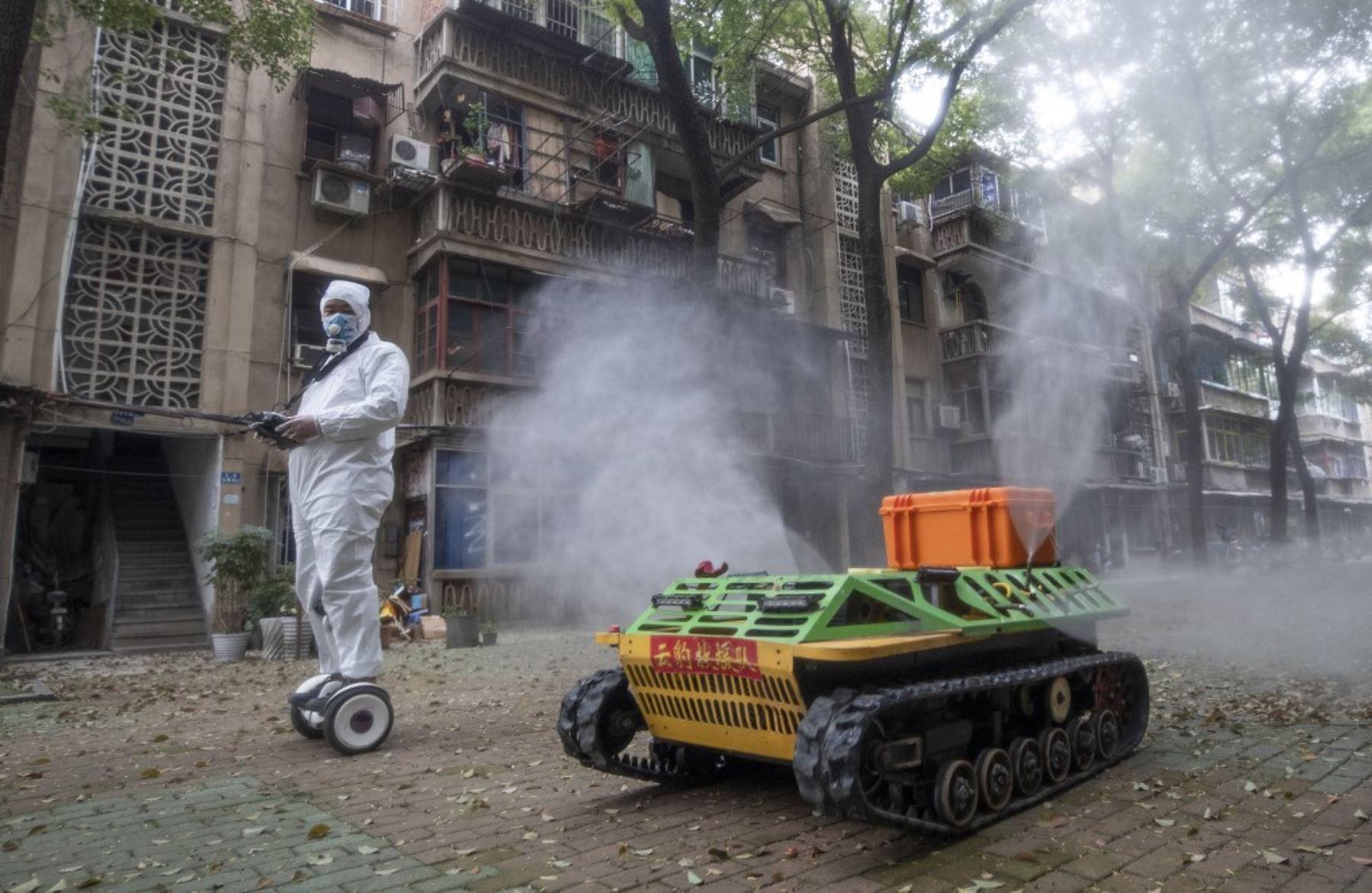 Un voluntario opera un robot de desinfección controlado a distancia para desinfectar un área residencial en medio del brote de coronavirus COVID-19 en Wuhan. Foto: AFP