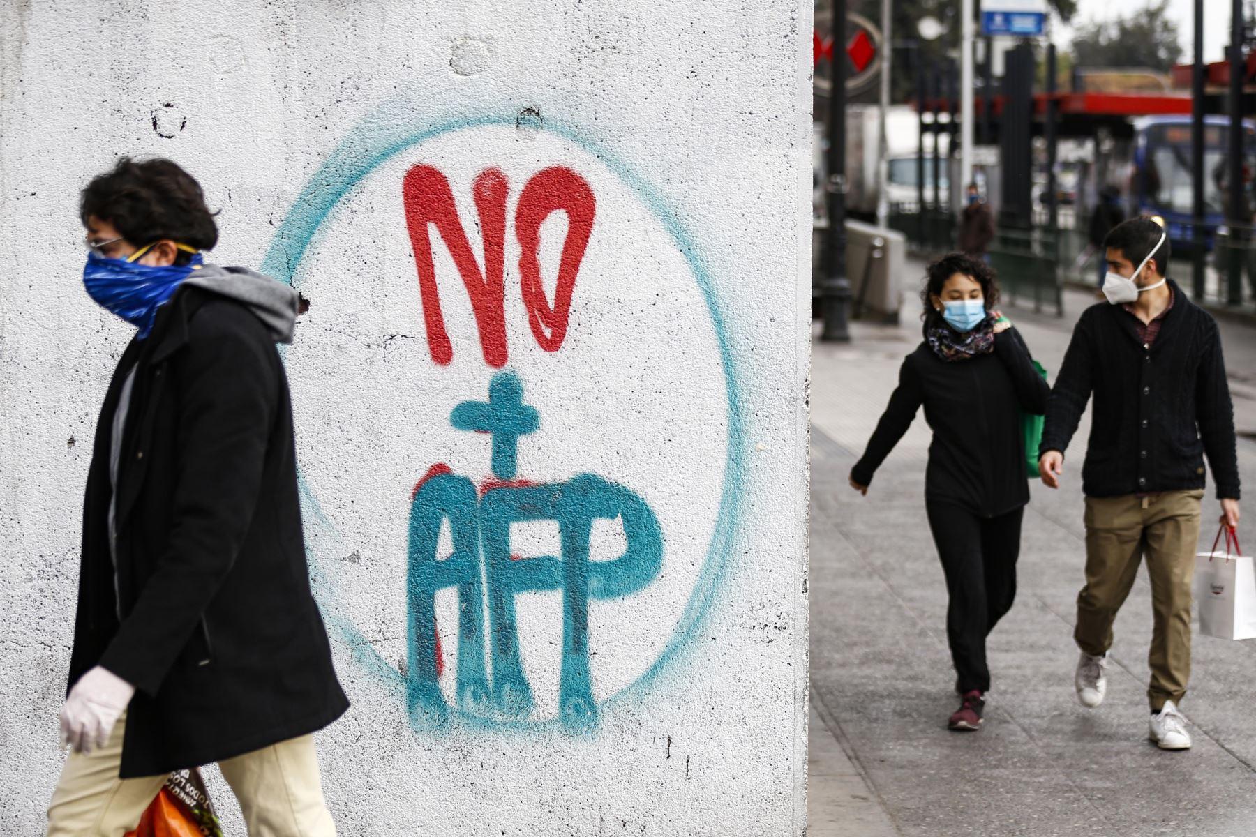 Gente camina cerca de un graffiti contra la Administración del Fondo de Pensiones (AFP) en Santiago. Foto: AFP