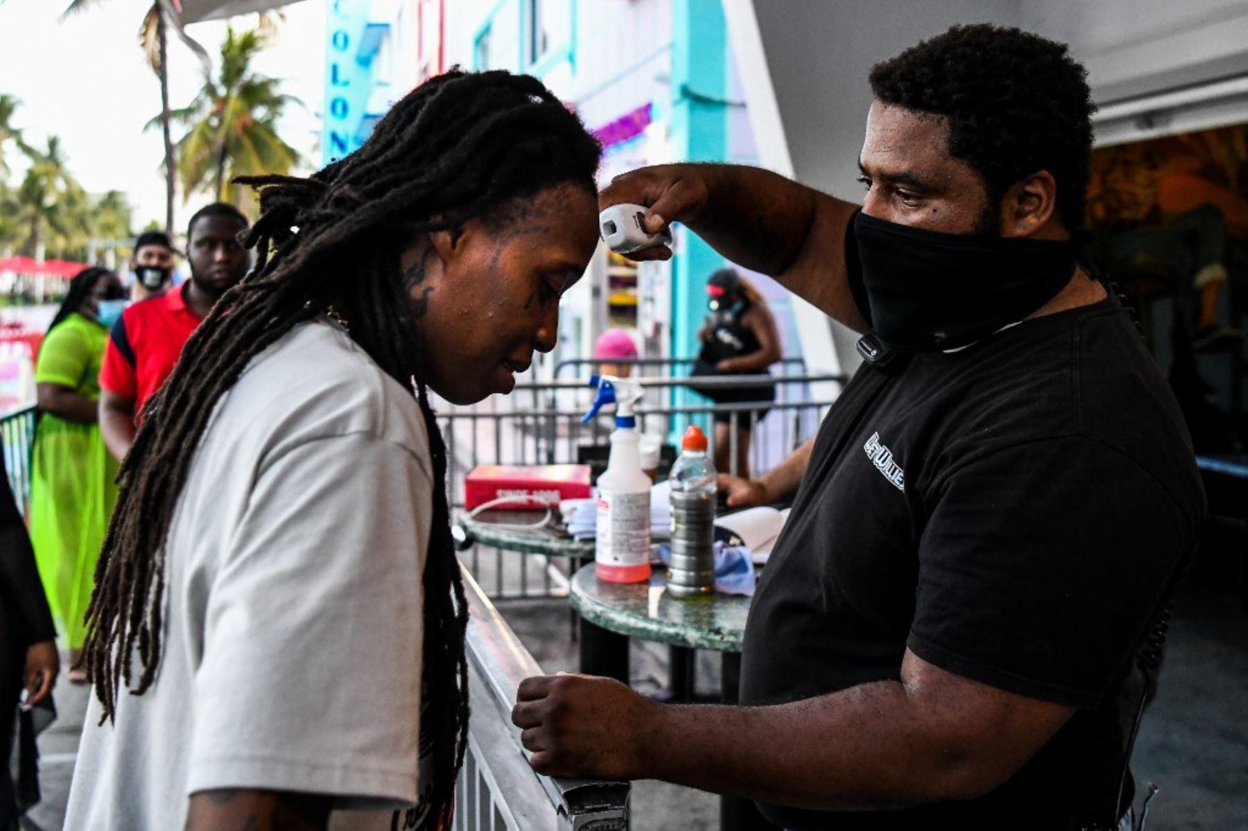 Un guardia de seguridad verifica la temperatura de un hombre a la entrada de un restaurante en Ocean Drive en Miami Beach, Florida. Foto: AFP